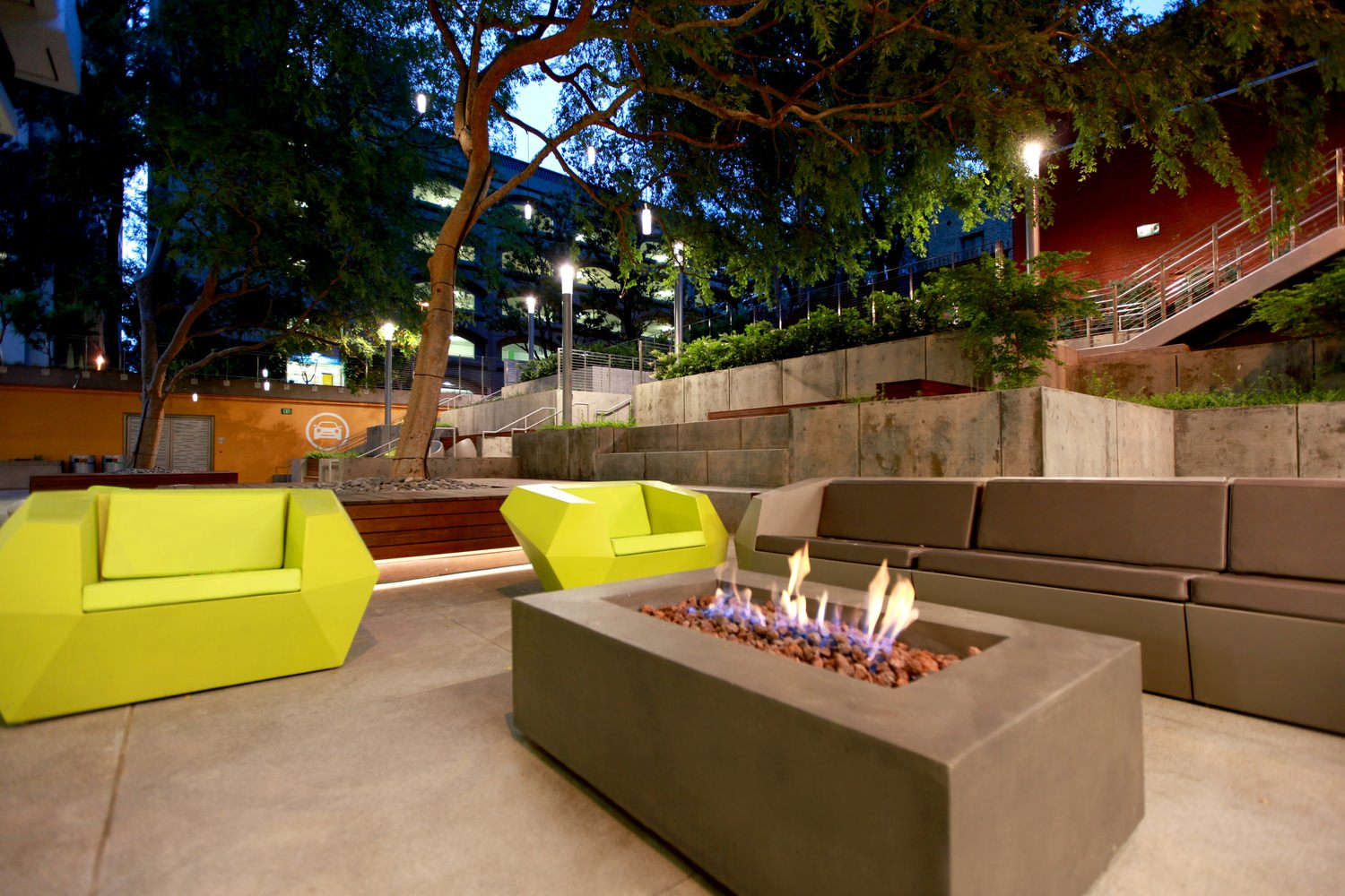 A sitting area features a fire place in a coffee table and many trees surrounding it.