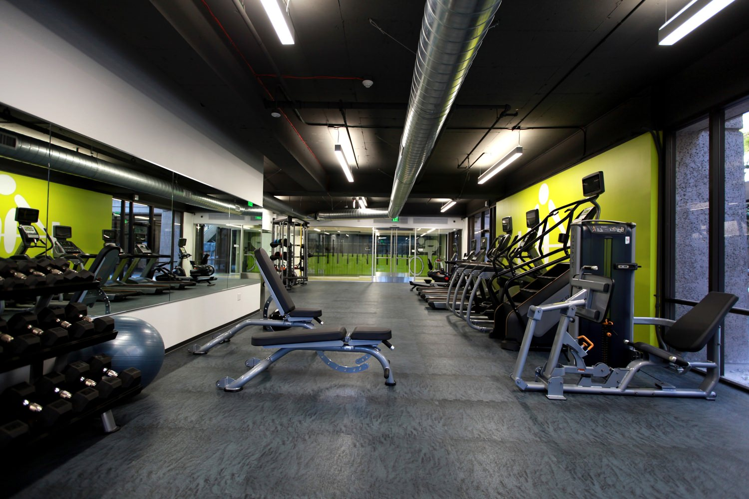 Gym that has a row of stair masters and other exercise equipment next to the walls and mirrors.