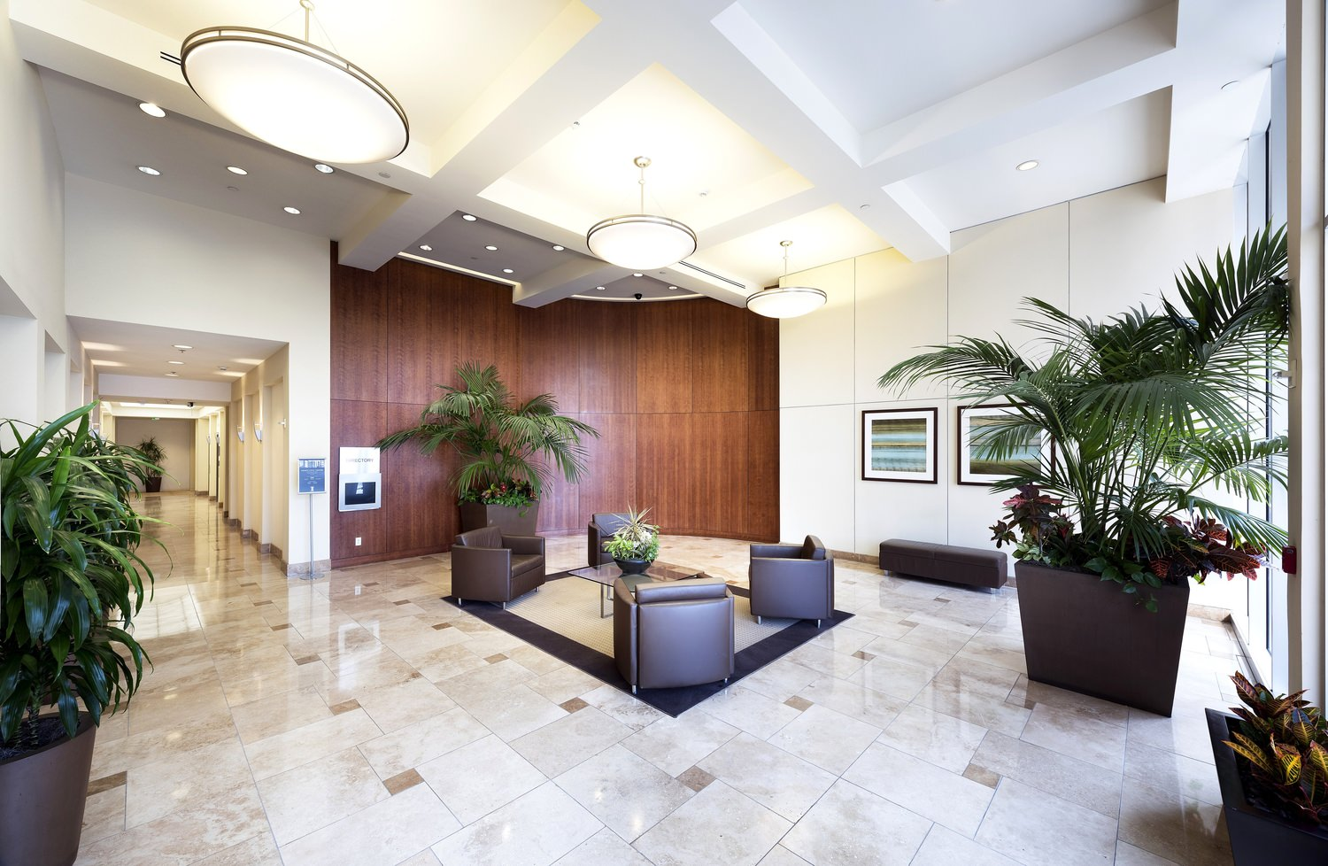Indoor lobby of a building that has plants and different furnitures like couches.