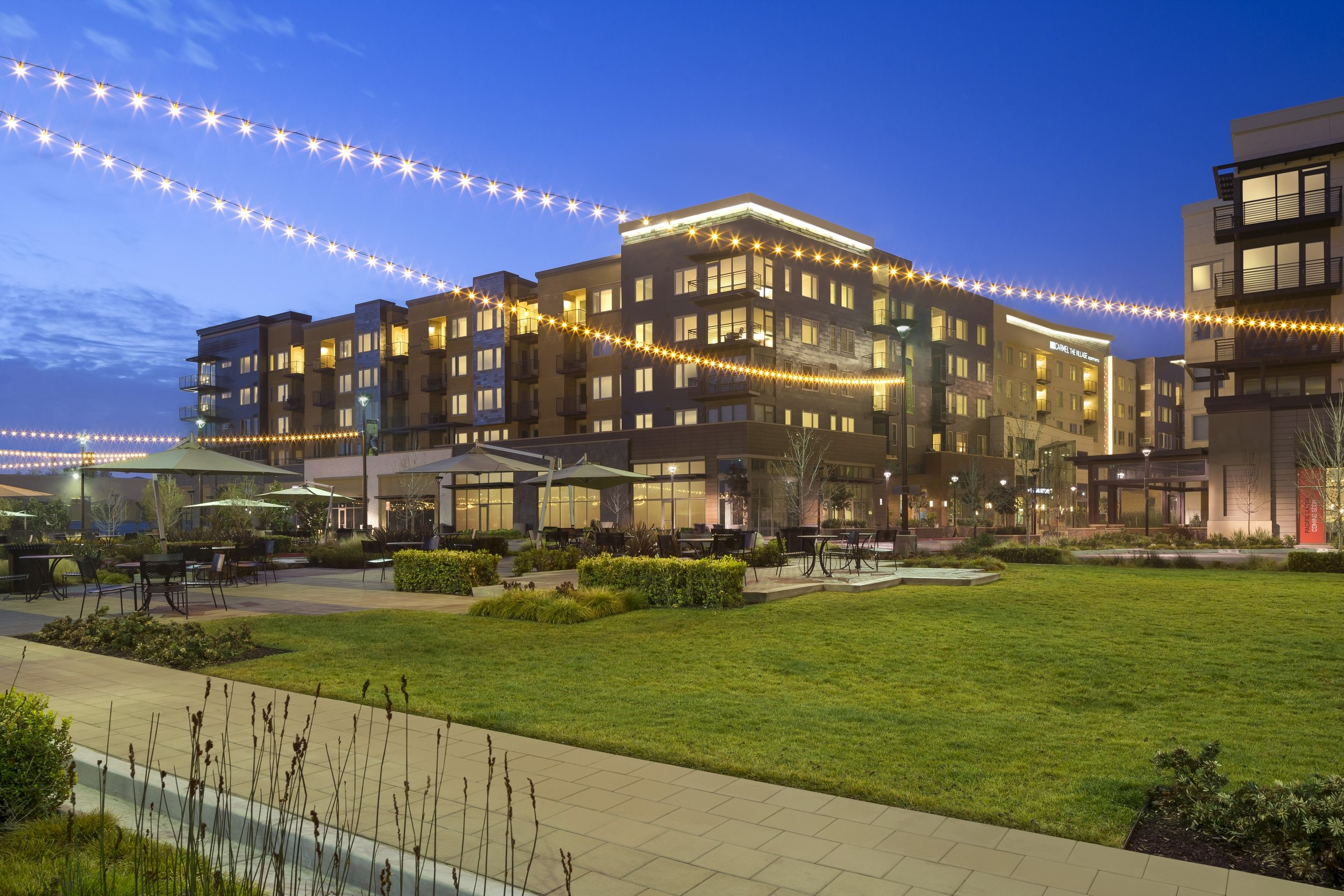 An outdoor patio and lawn full of grass in front of a large building with the night blue sky in the