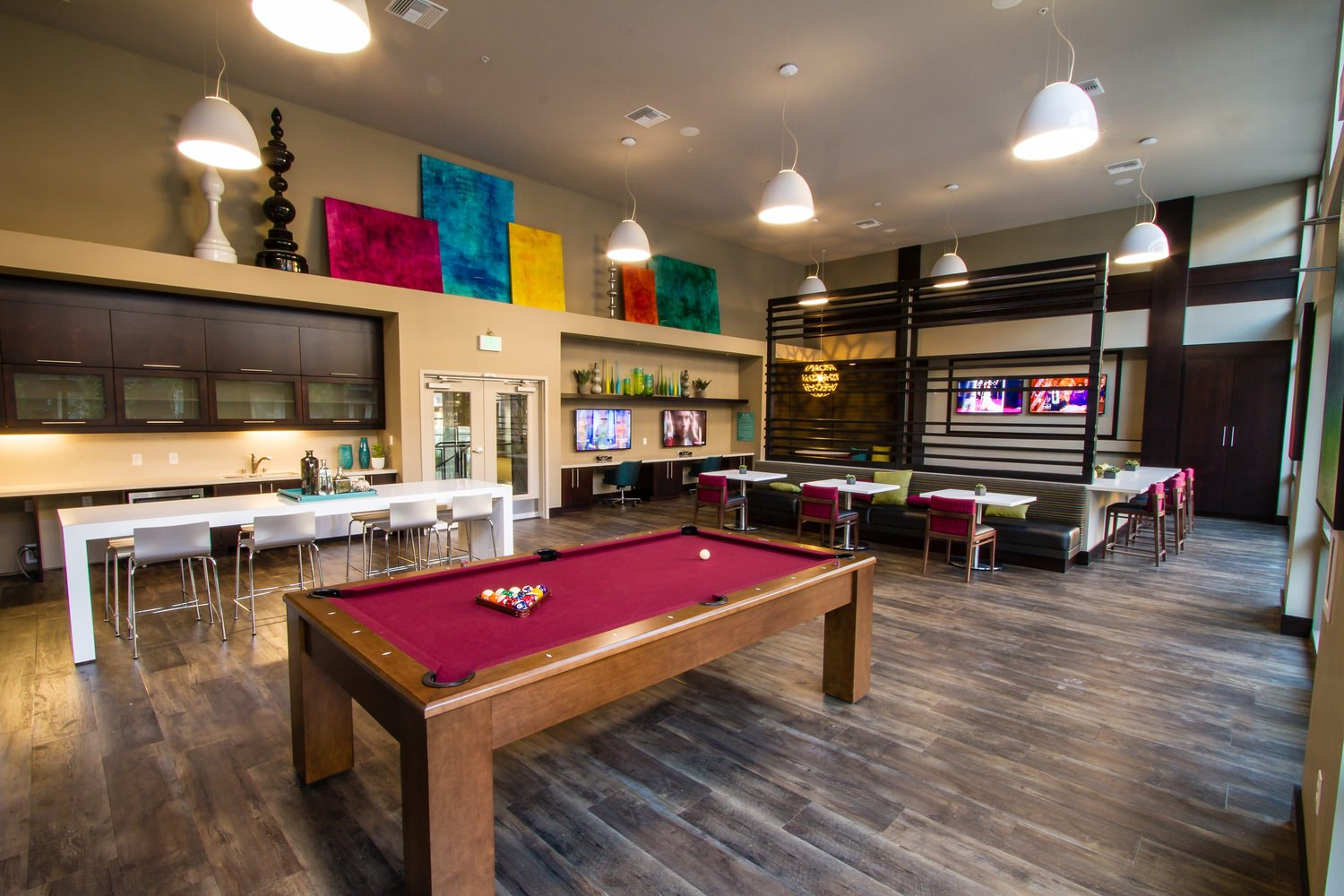 A game room that has a pool table and kitchen table and chairs behind it next to some cabinets.