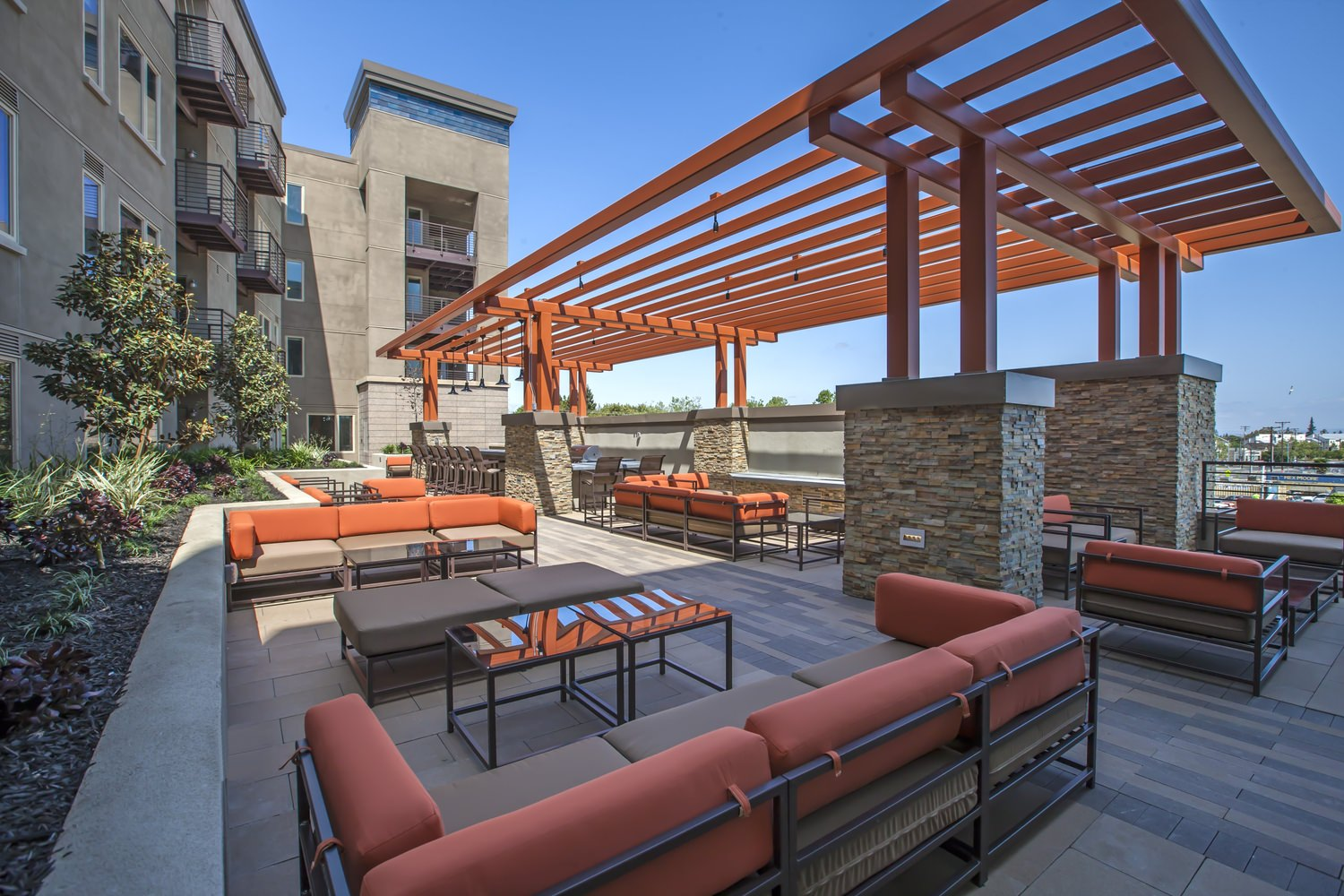 An outdoor pation full of orange and brown furniture that is next to a building made of bricks.