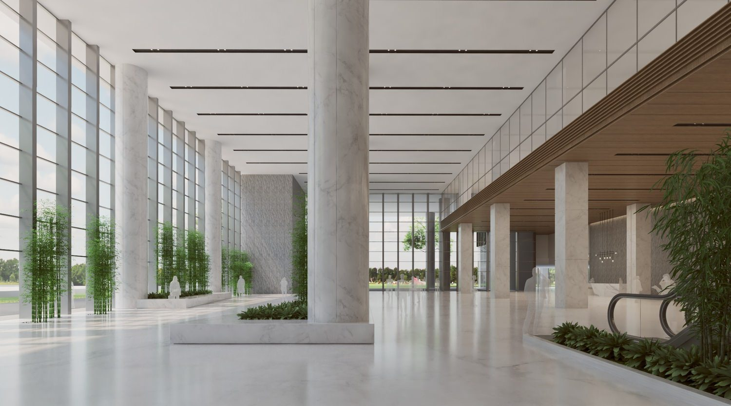 The lobby of a large building that has floor to ceiling windows and white marble wrapped columns in the middle of it.