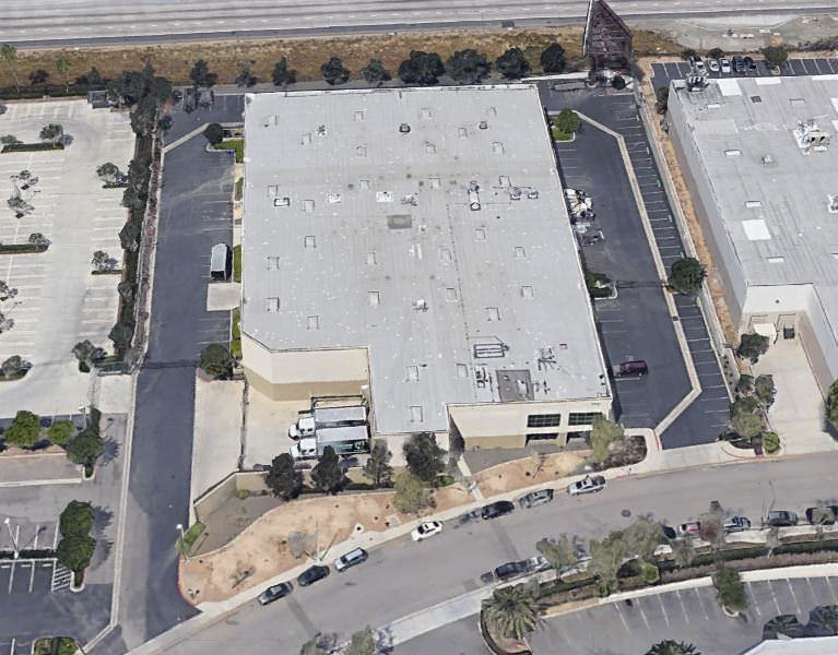 Top view of a few white warehouses that has cars and trucks parked in the lot around it.