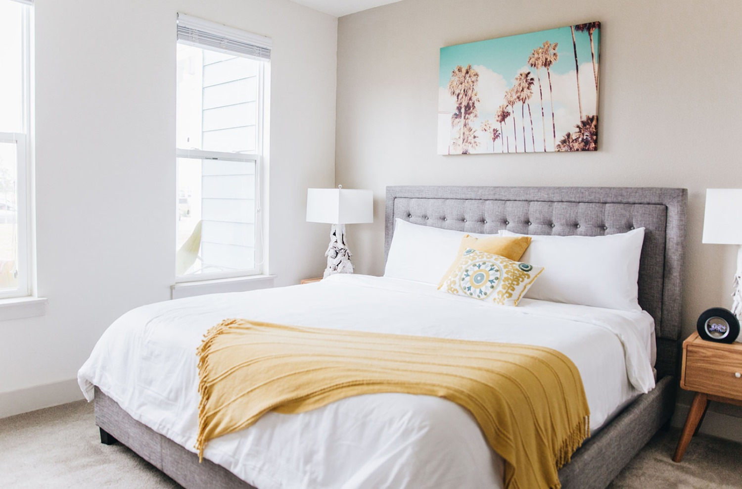 A bedroom with a bed that is covered in pillows and white sheets that is next to a window.