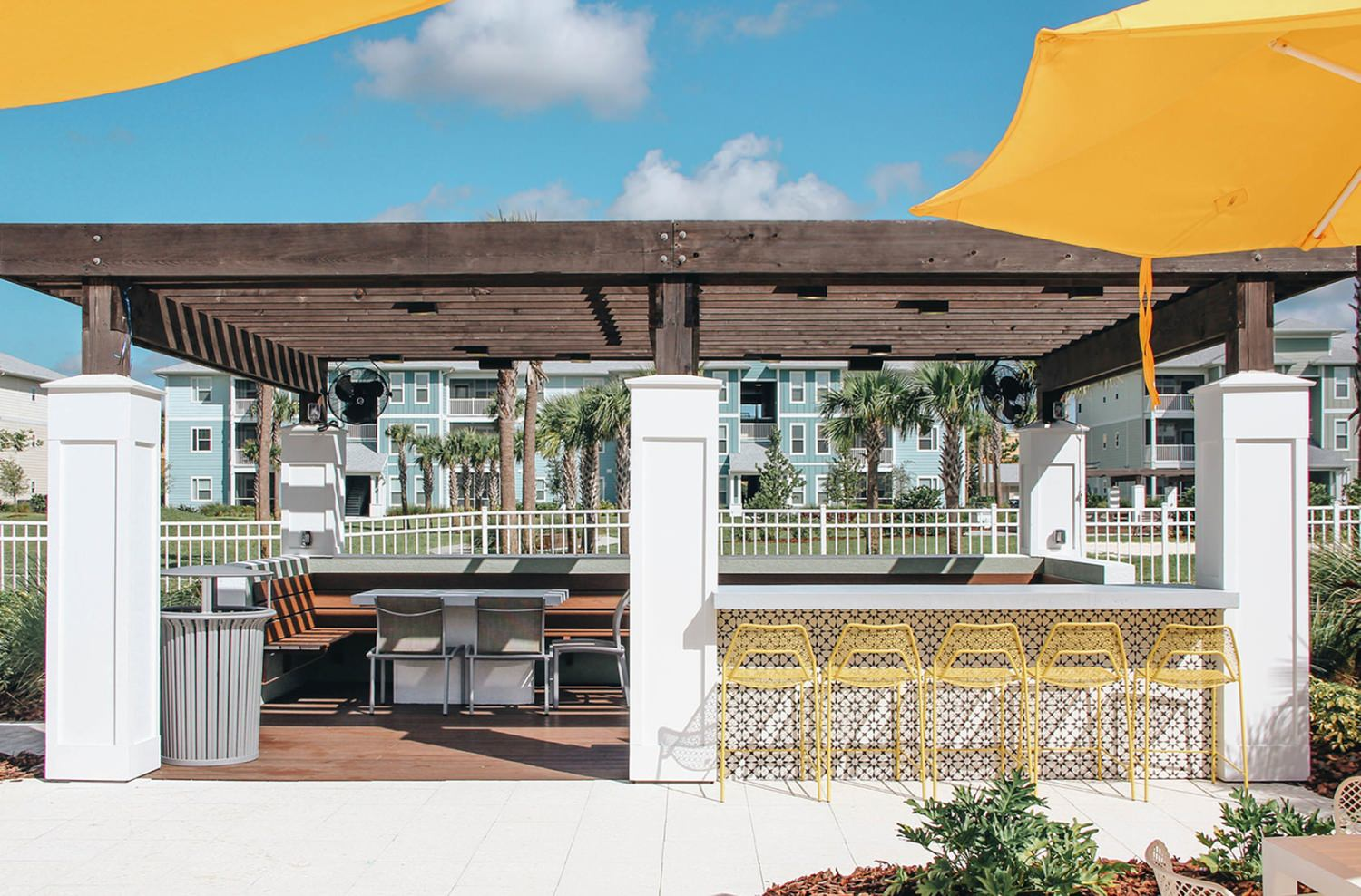 A building next to a open patio that is full of chairs and tables with umbrellas.