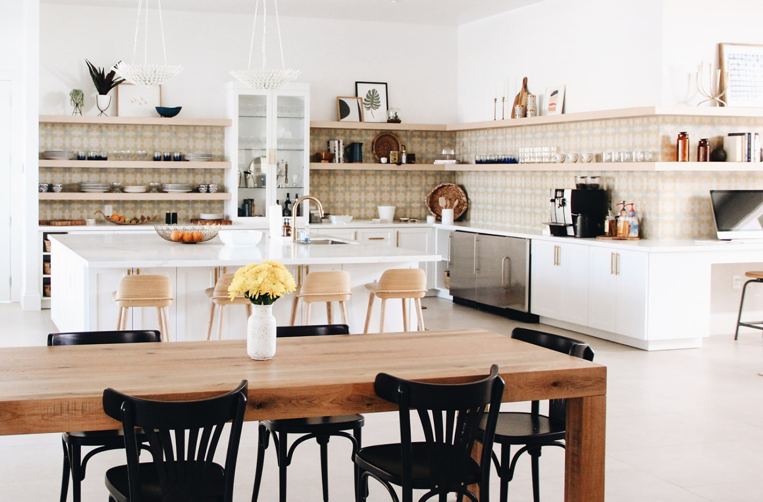 A large kitchen with white cabinets and wall painted white got furnished on the floor with wooden furniture.