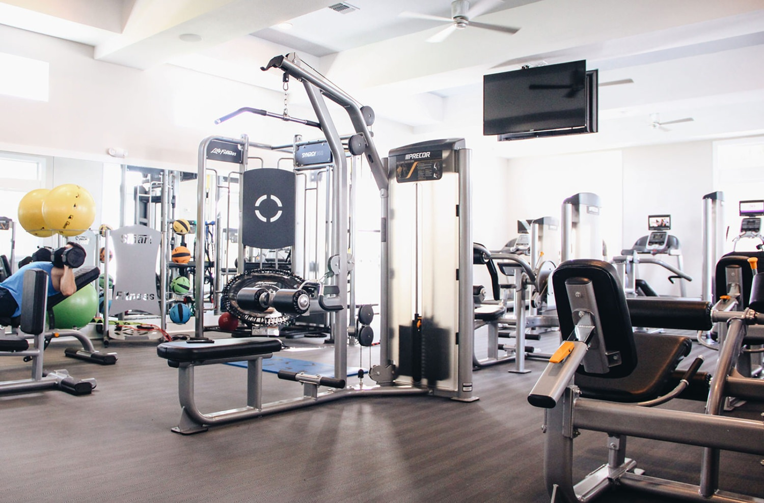A few people inside of a gym room full of weight machines and other exercise equipment.