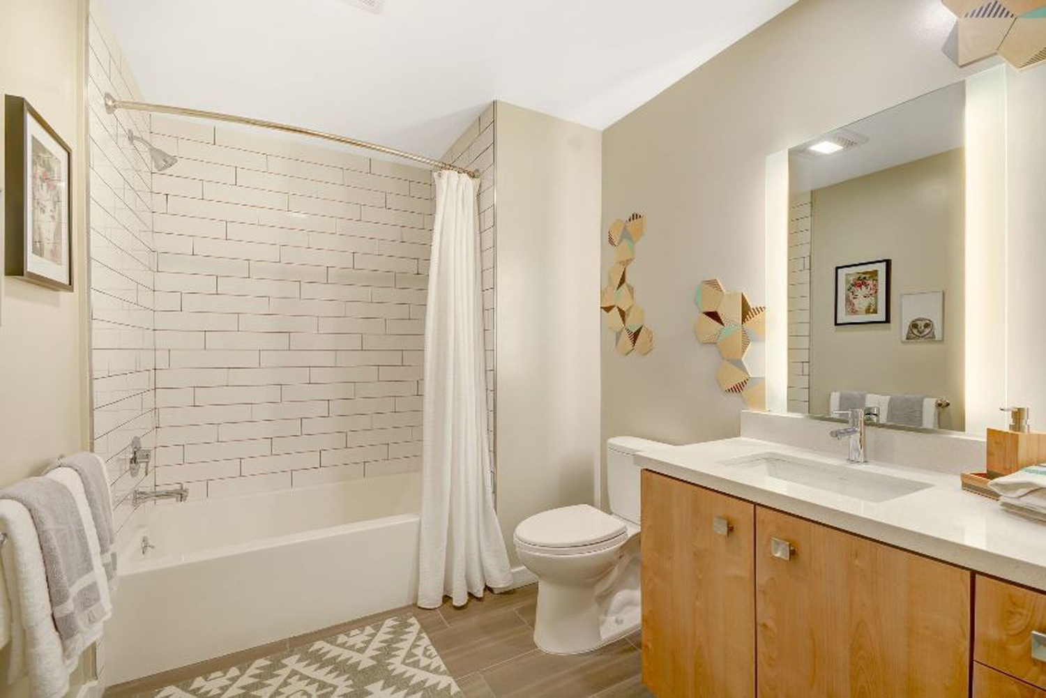A bathroom that is decorated with white walls and tiles on the floor and shower.