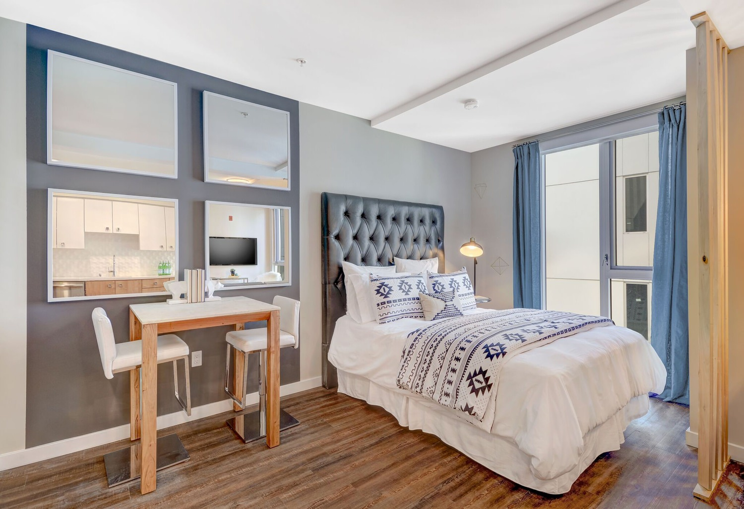 A bedroom with a a desk and chair that is next to a bed covered in white linens.
