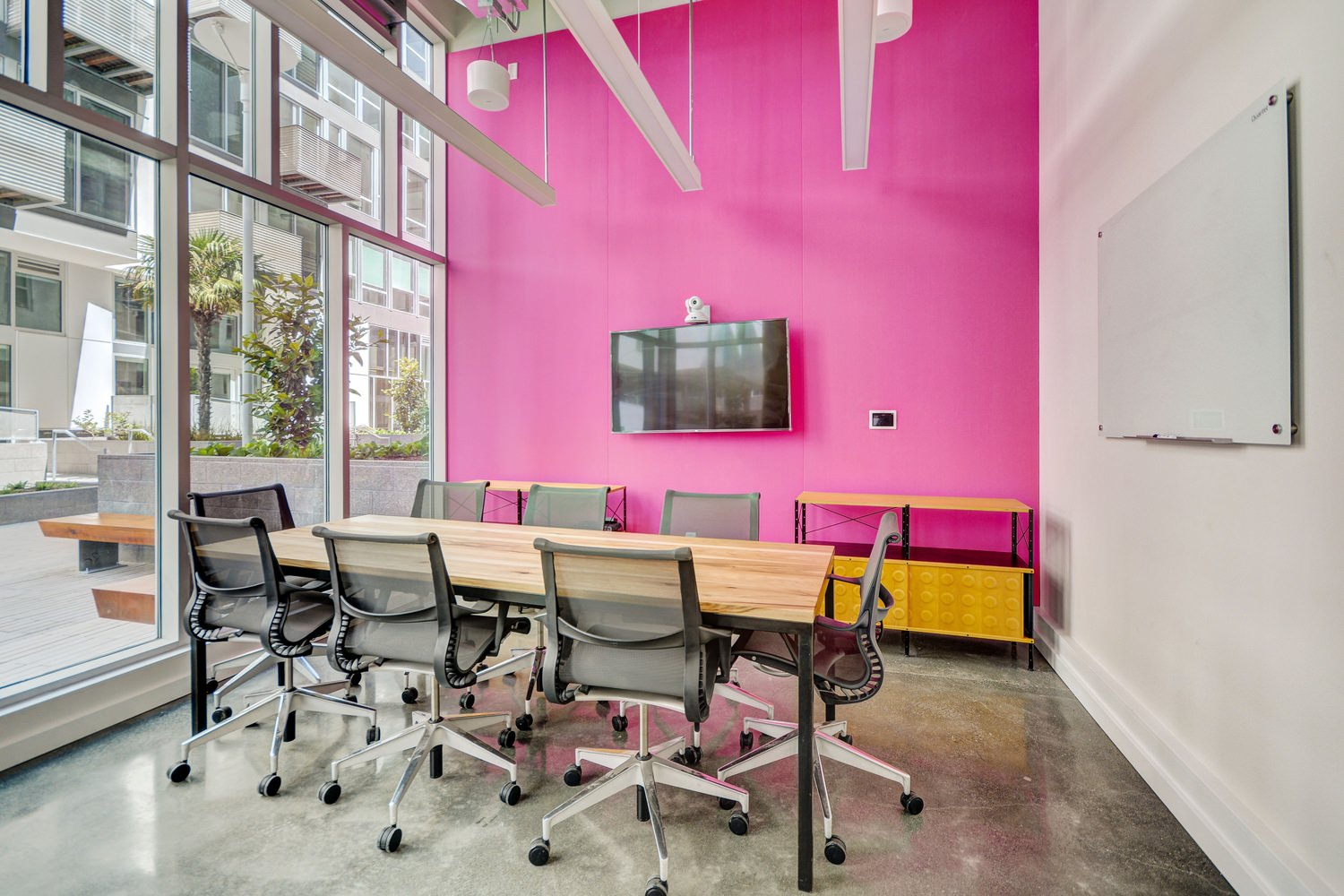 An office with a long table that is surrounded by chairs and next to a pink wall.