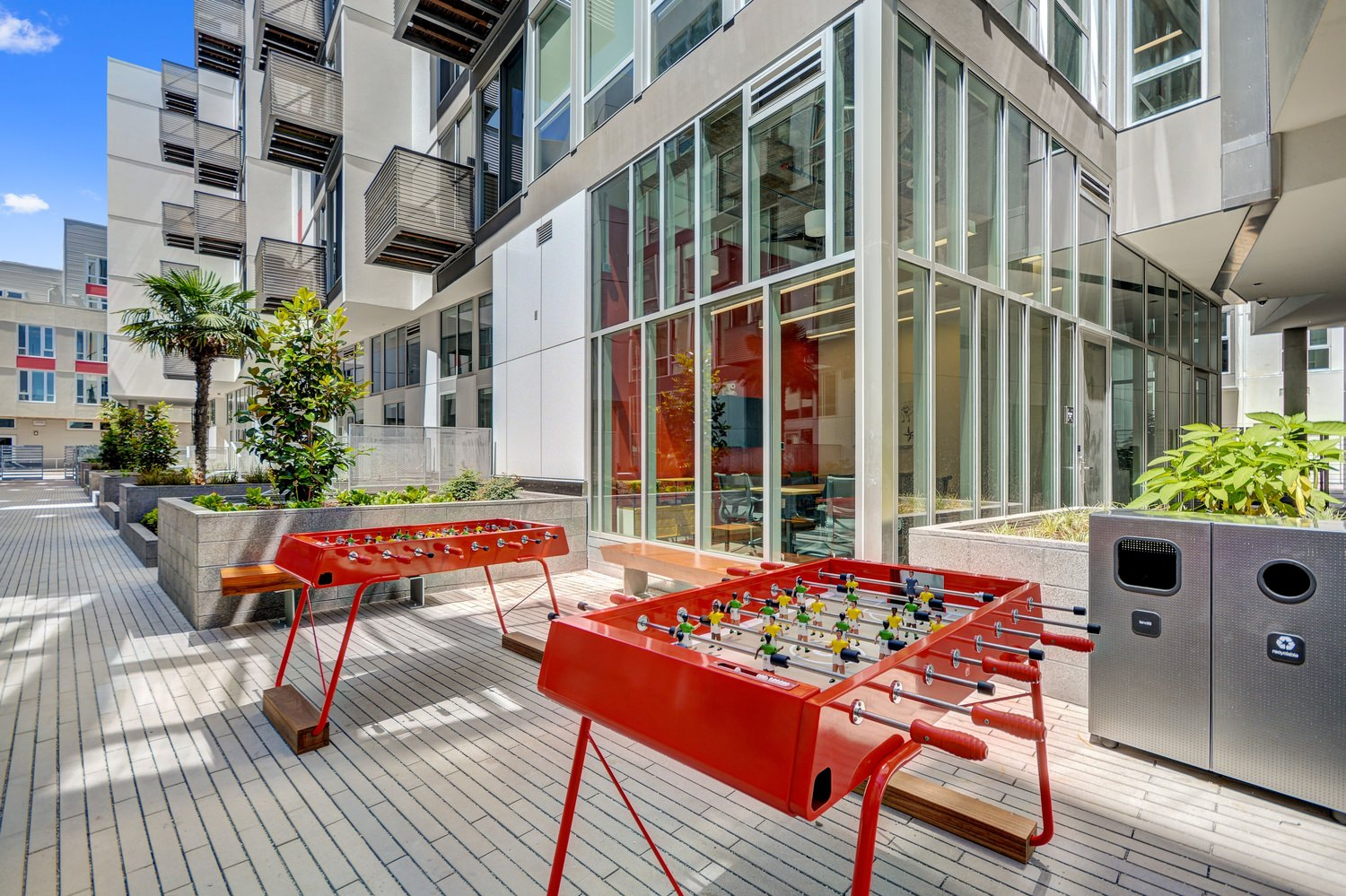 A walkway that is line with game tables and plants that is next to a large building with windows.