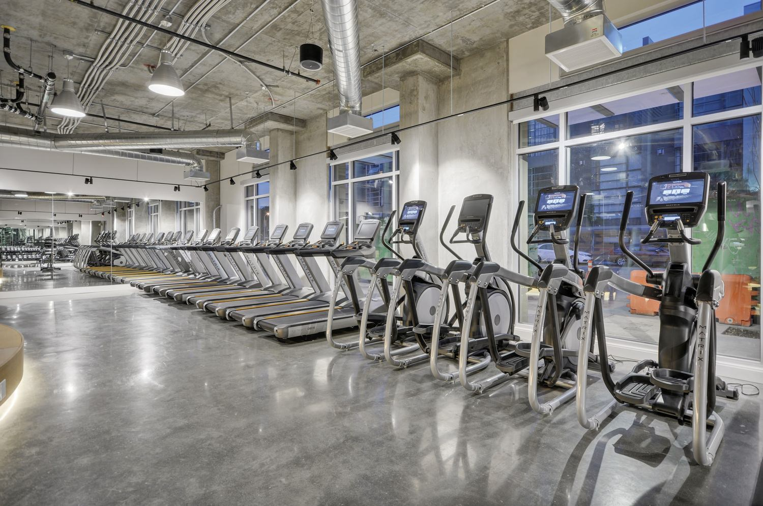A row of several exercise bikes and treadmills line the indoor room of a gym with glass windows.