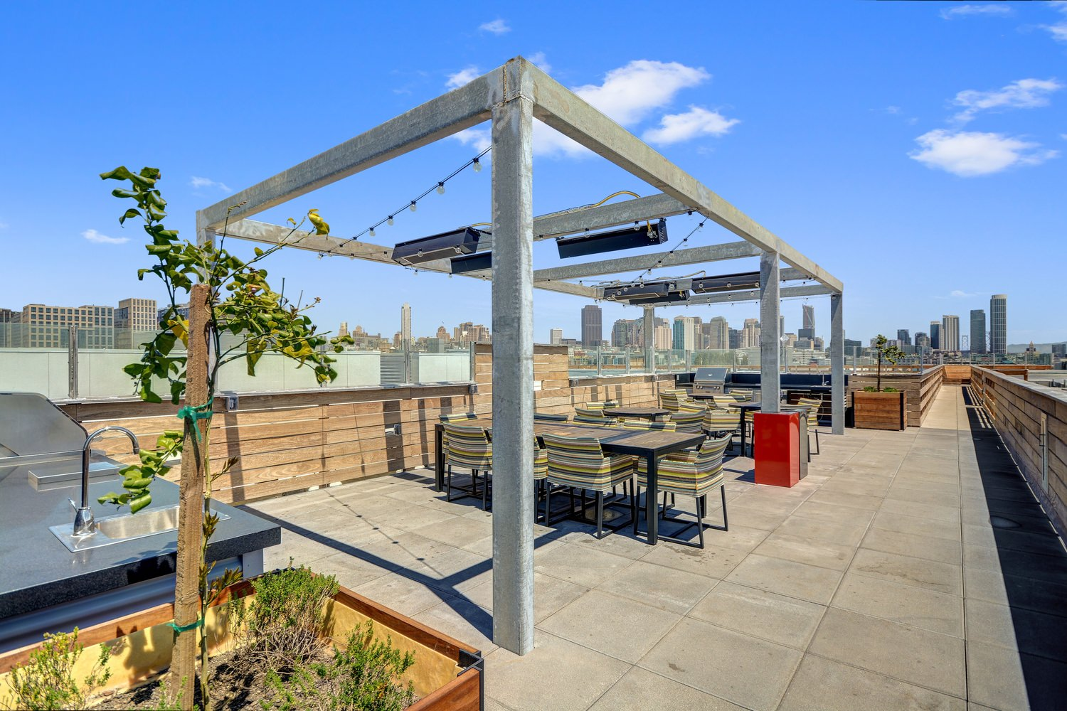 A rooftop patio with tables and chairs setup beneath a pergola strung with lights.