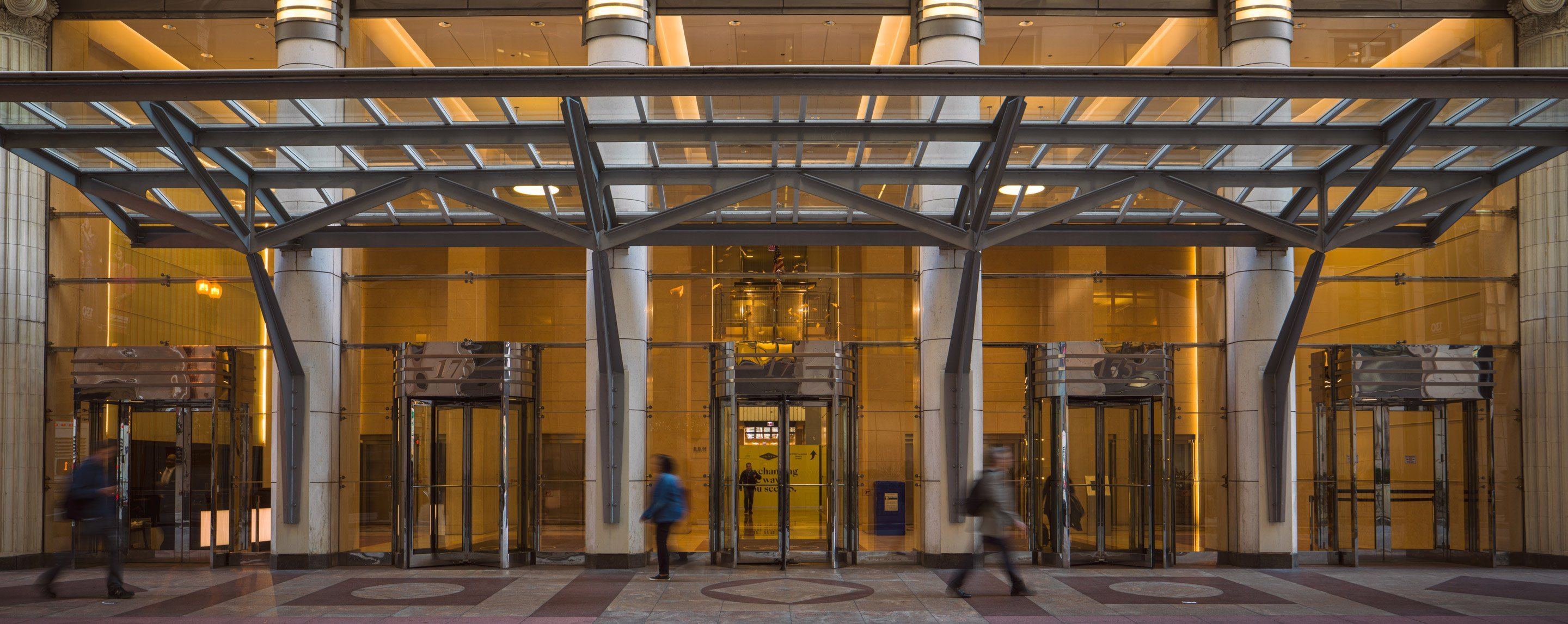 People walk past a glass entryway to a large building with five revolving doors.