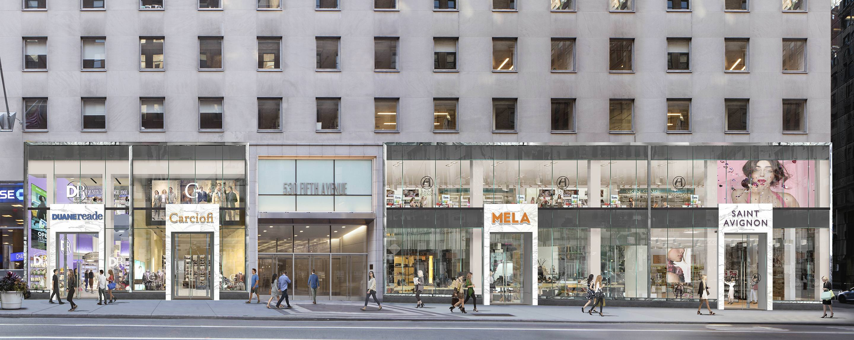 People walk on the sidewalk outside of the building housing stores such as Saint Avignon and Mela.
