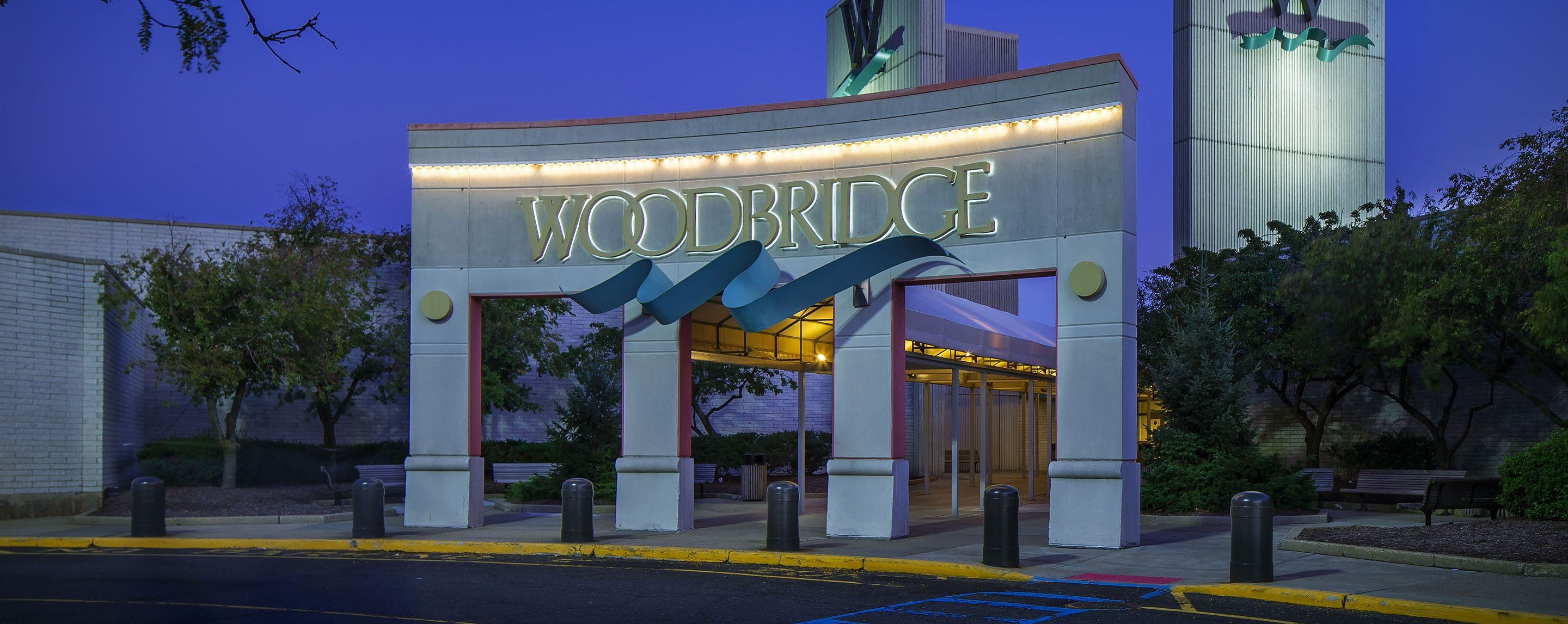 An ornate archway advertises the entrance for the Woodbridge Mall. A blue ribbon decoration underlin