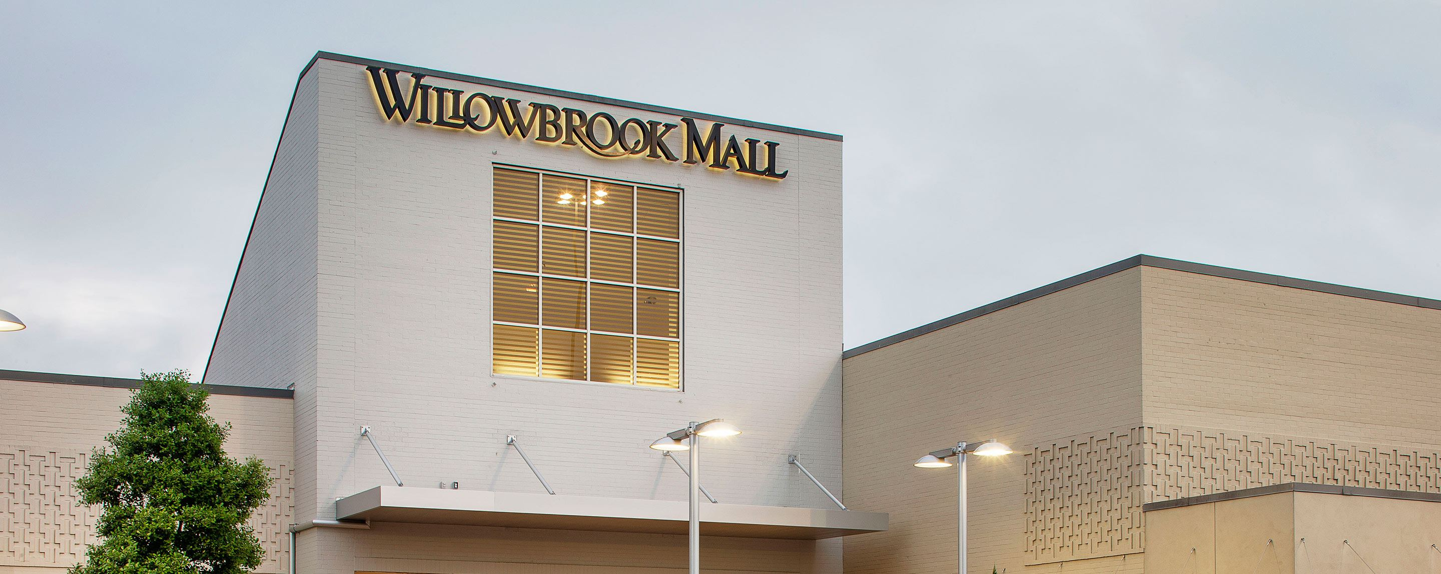 """""""Willowbrook Mall"""" is printed in dark lettering above the large square window of an indoor shopping"""