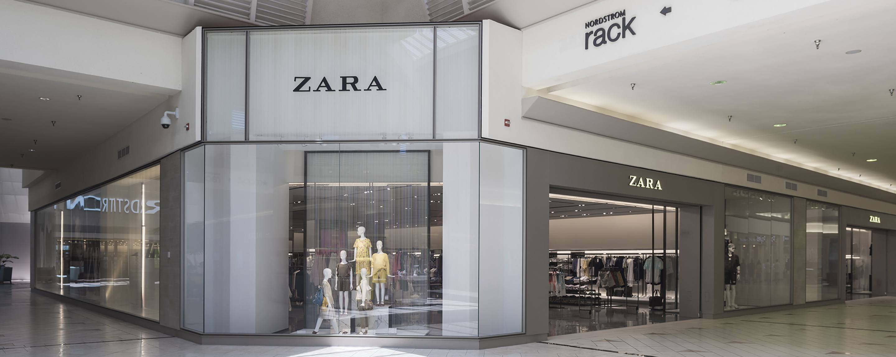 A family of brightly dressed mannequins inside of a Zara in a modern, tiled mall with gray walls.