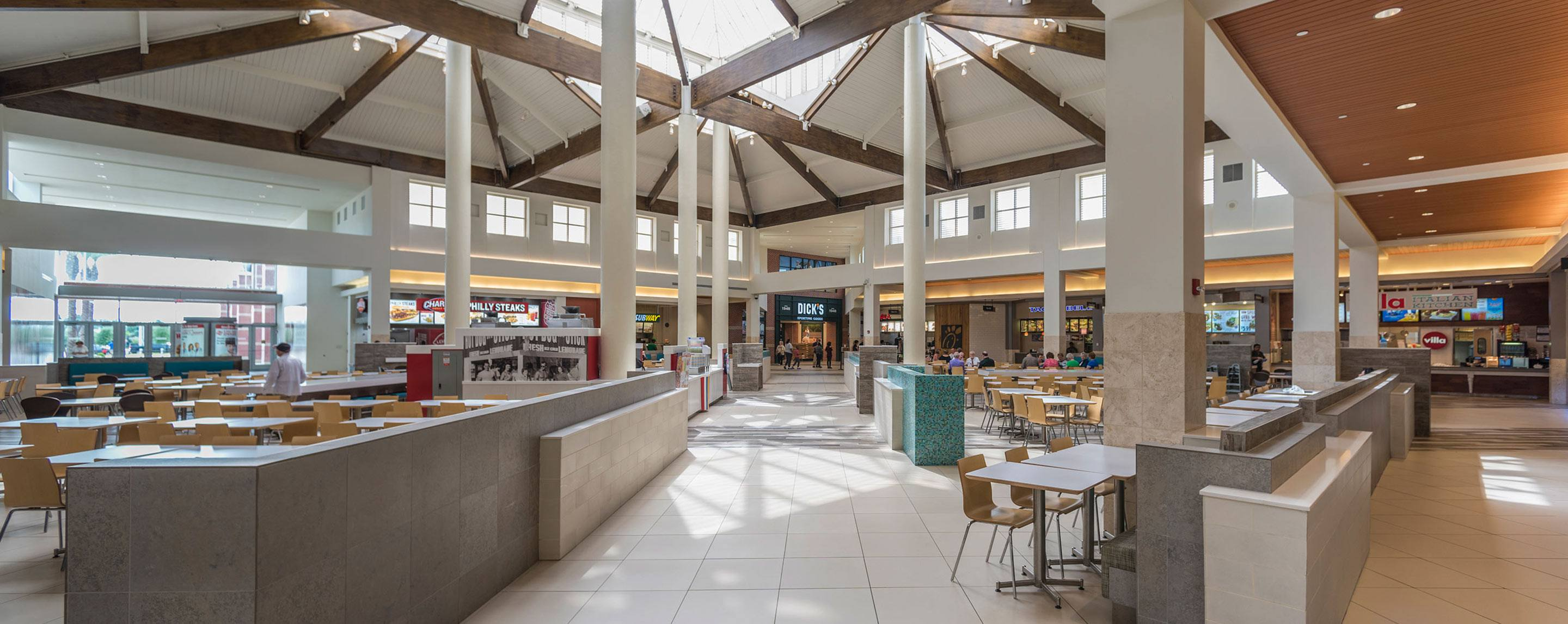 Booths and tables stand in a mall food court. Restaurants including Subway line the sides.