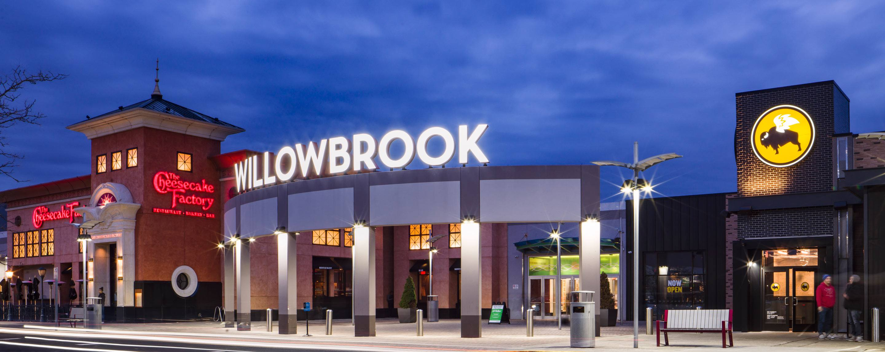 "A bright ""Willowbrook"" sign is illuminated at dusk. Nearby are The Cheesecake Factory and Buffalo Wi"