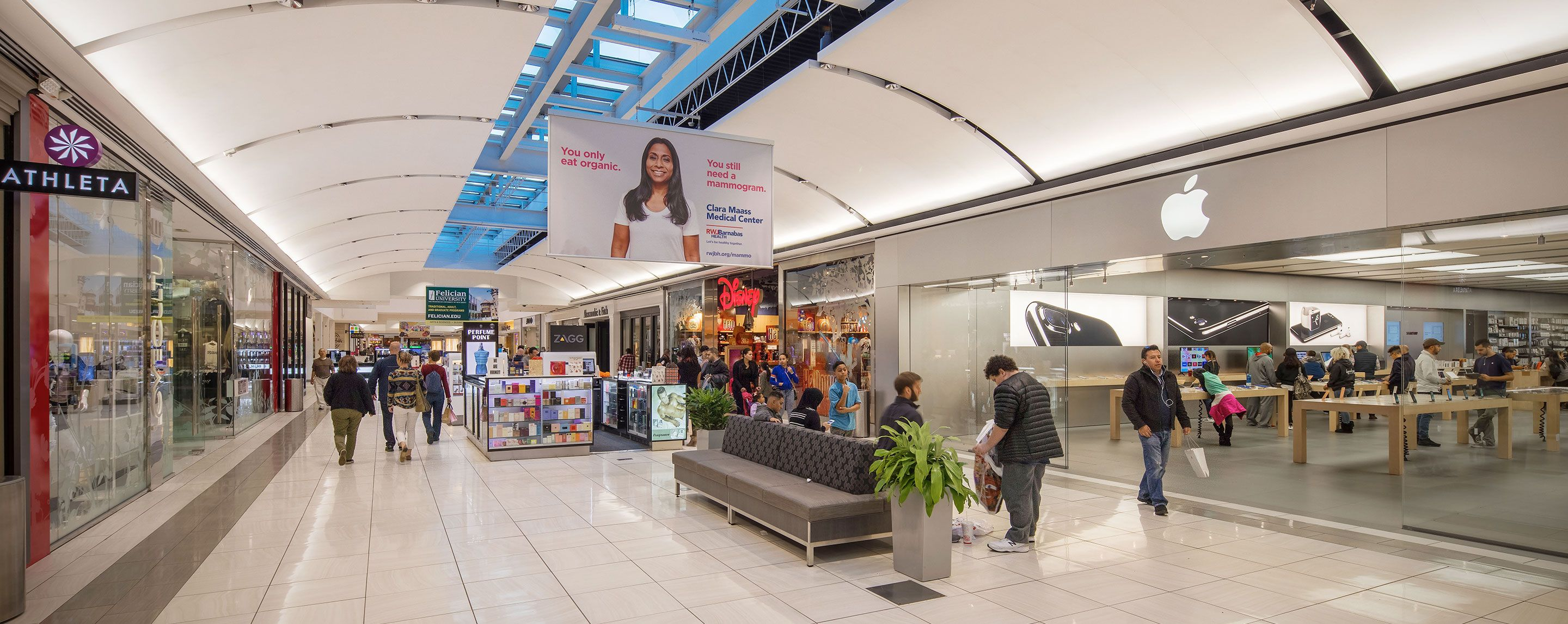 A mall with several people and the stores Athleta and Apple visible.
