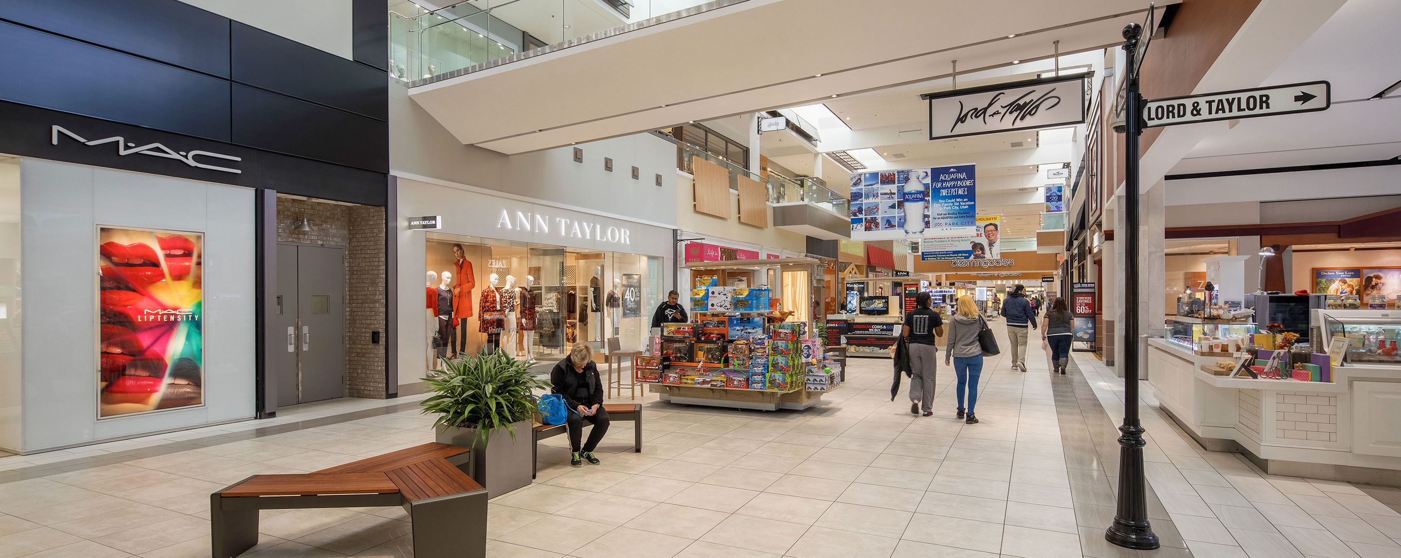 MAC and Ann Taylor are near a person on a bench and a toy kiosk at an indoor mall.
