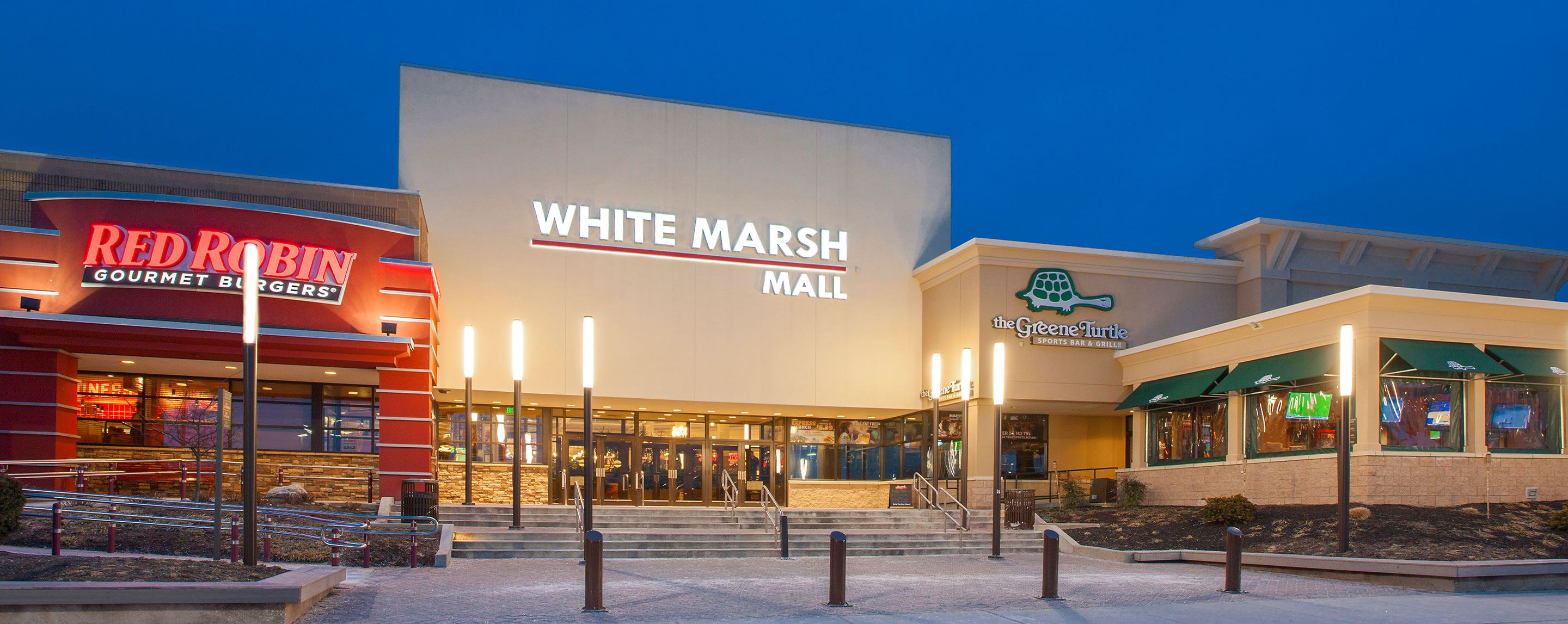 An exterior shot of the White Marsh Mall at twilight. A Red Robin storefront stands to the left.