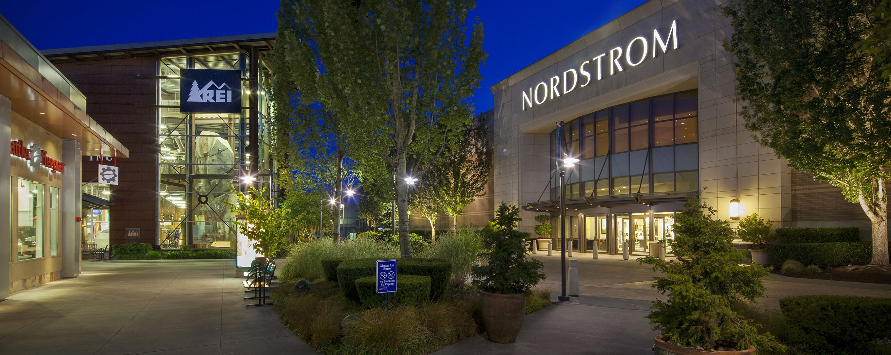 A Nordstrom store stands across from other stores in the middle of an outdoor shopping center.