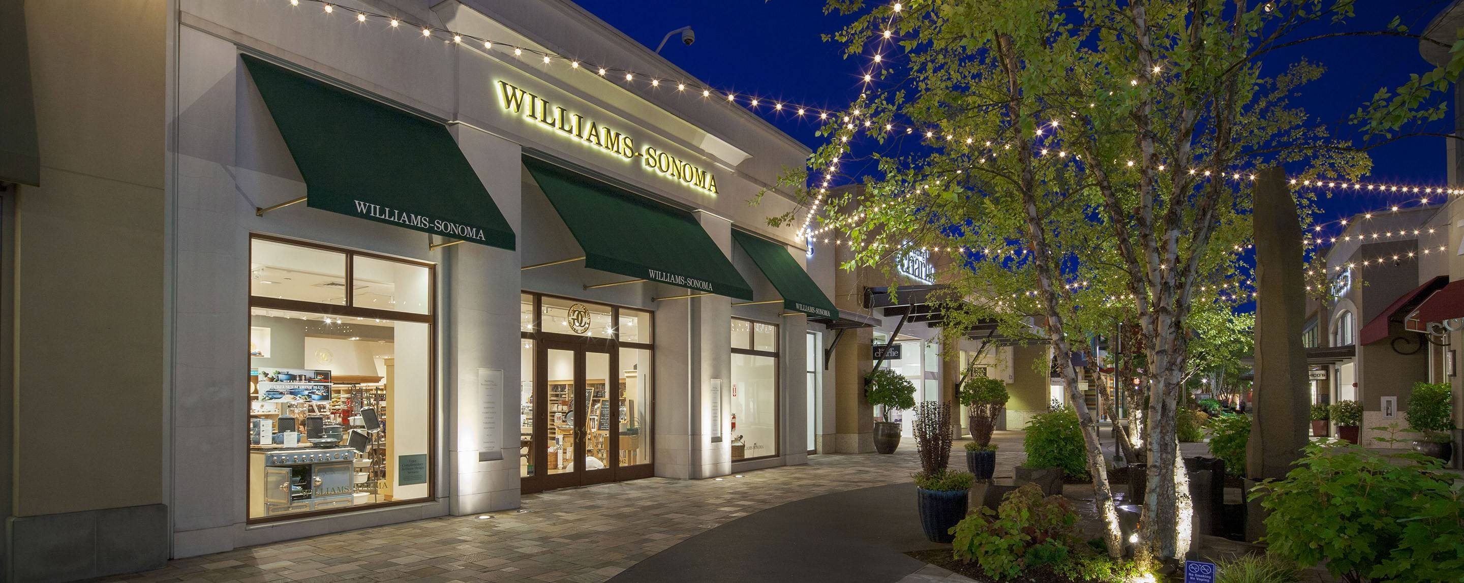 There is a tree and hanging lights outside of a Williams Sonoma store.