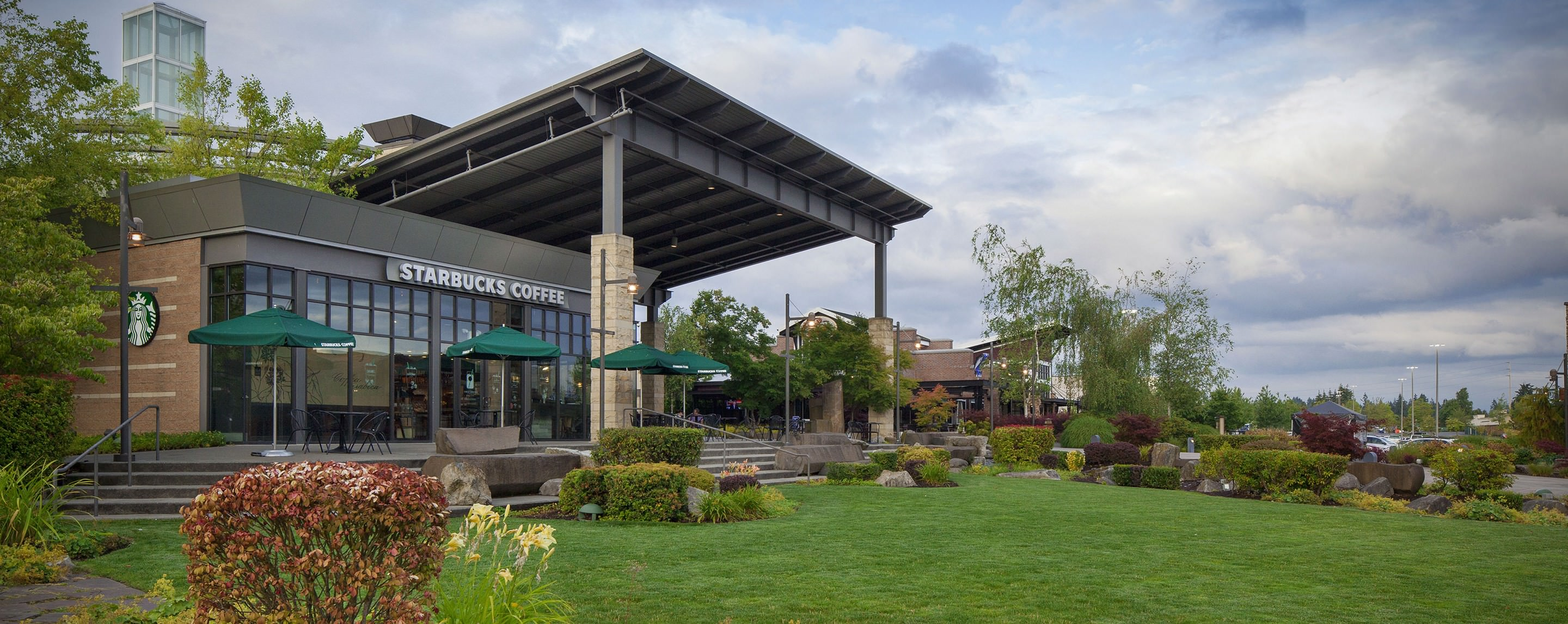 A Starbucks Coffee shop with a large veranda and outdoor patio area compete with a grassy lawn and assorted hedges.