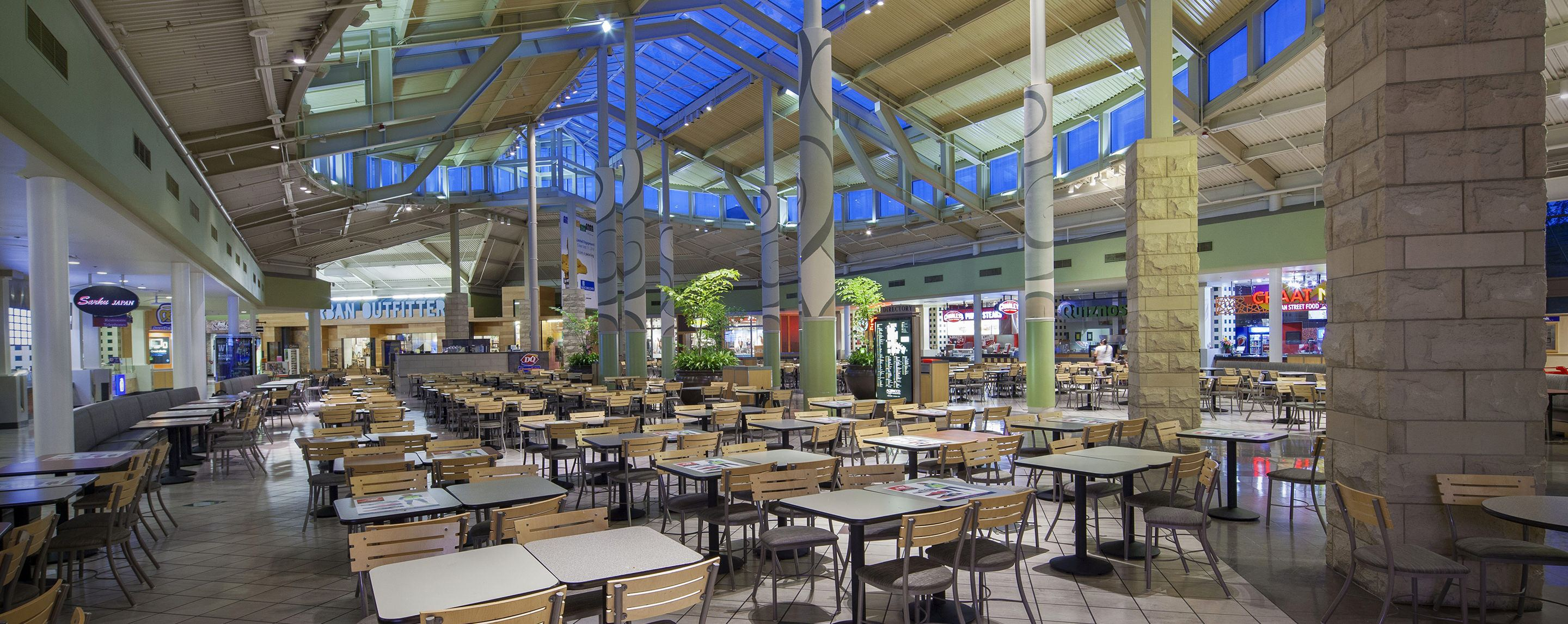 Rows of tables sit under a glass roof in an indoor mall. The tables are mostly empty.