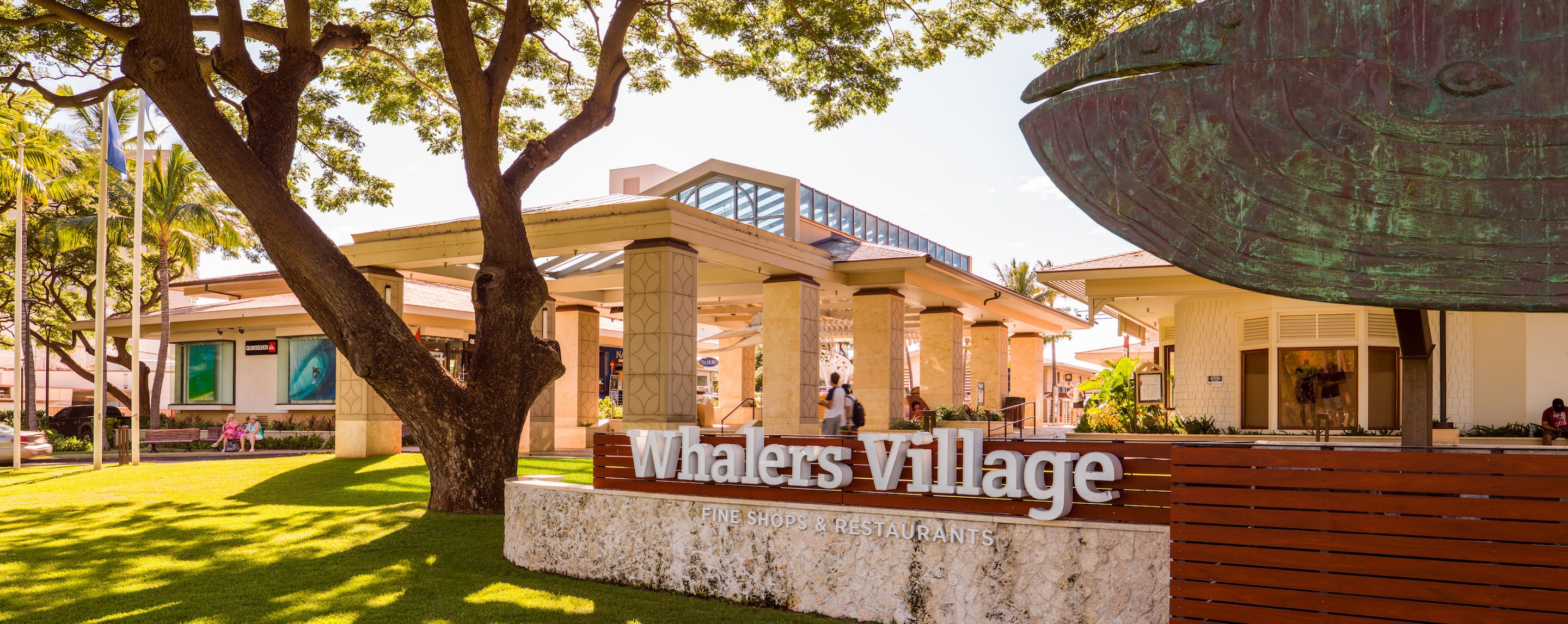 A photograph of a sign reading Whalers Village. Behind the sign stands a large building.