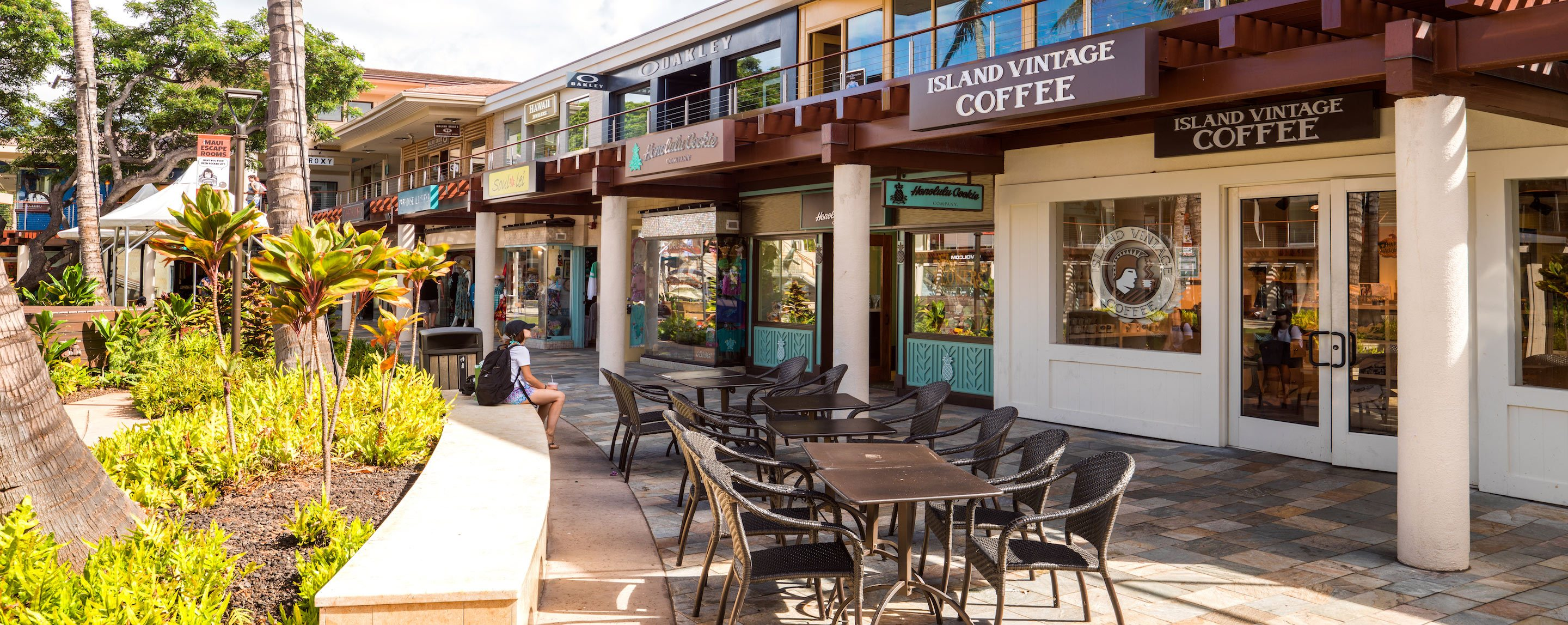 Tables and benches stand outside store fronts in an outdoor mall. The stores include Lava and Starbucks.