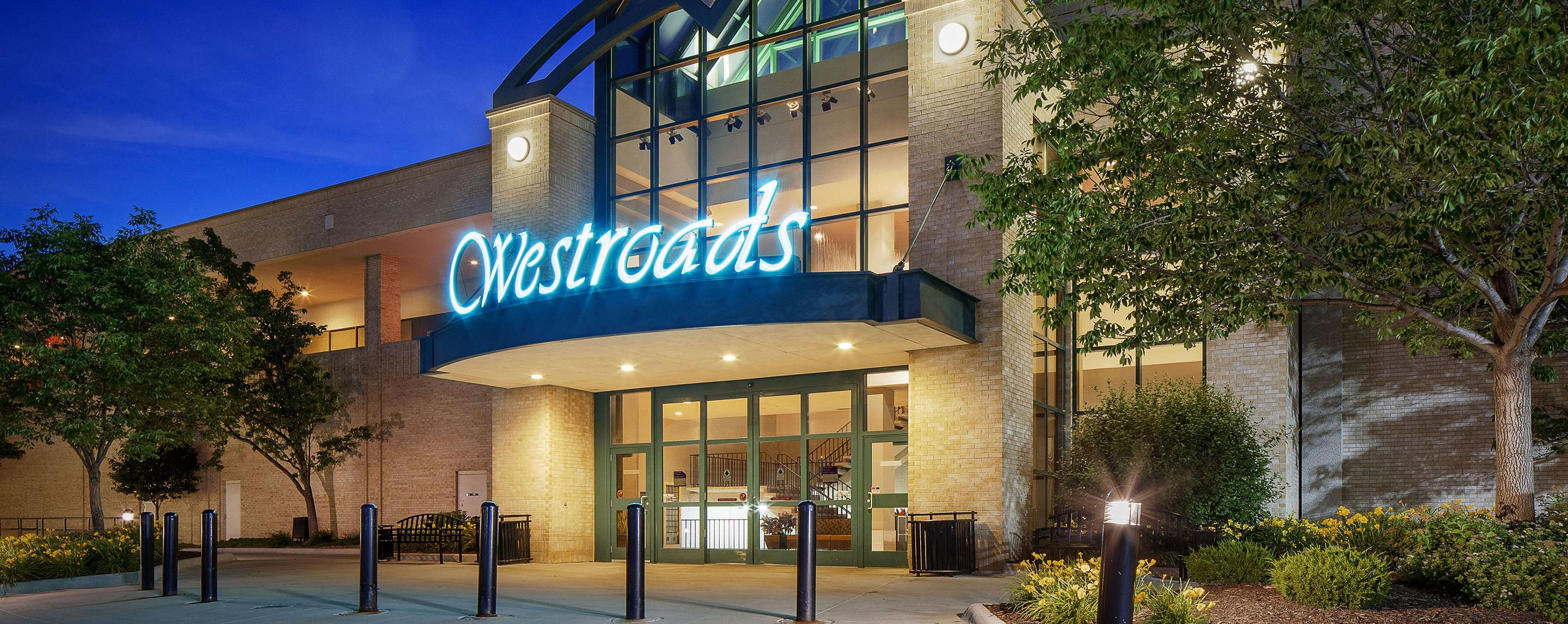 A large building with tall glass doors and a sign that says Westroads.