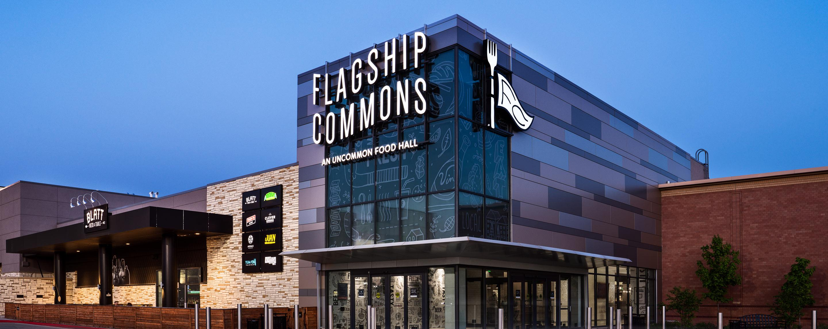 """A tall building with a face of glass windows has the words """"Flagship Commons"""" written on the front."""