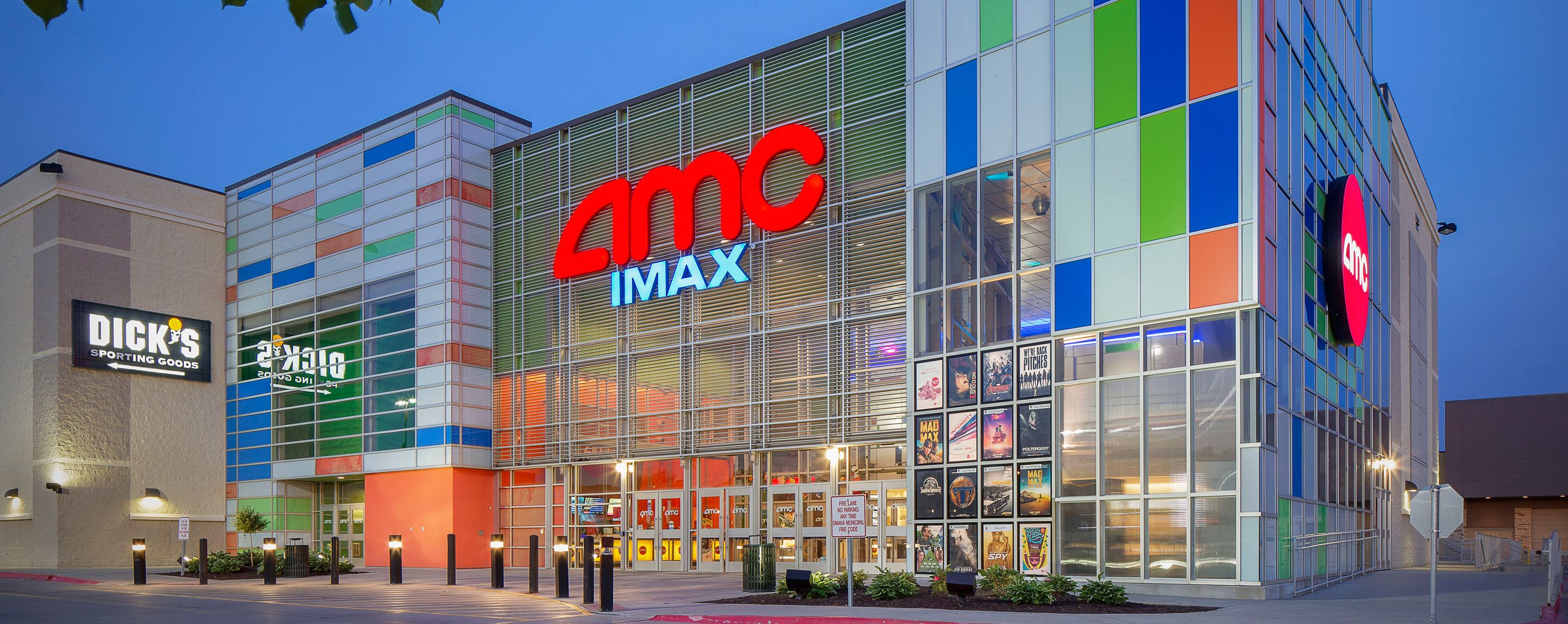 An AMC IMAX building stands in a complex next to a Dick's sporting goods store.