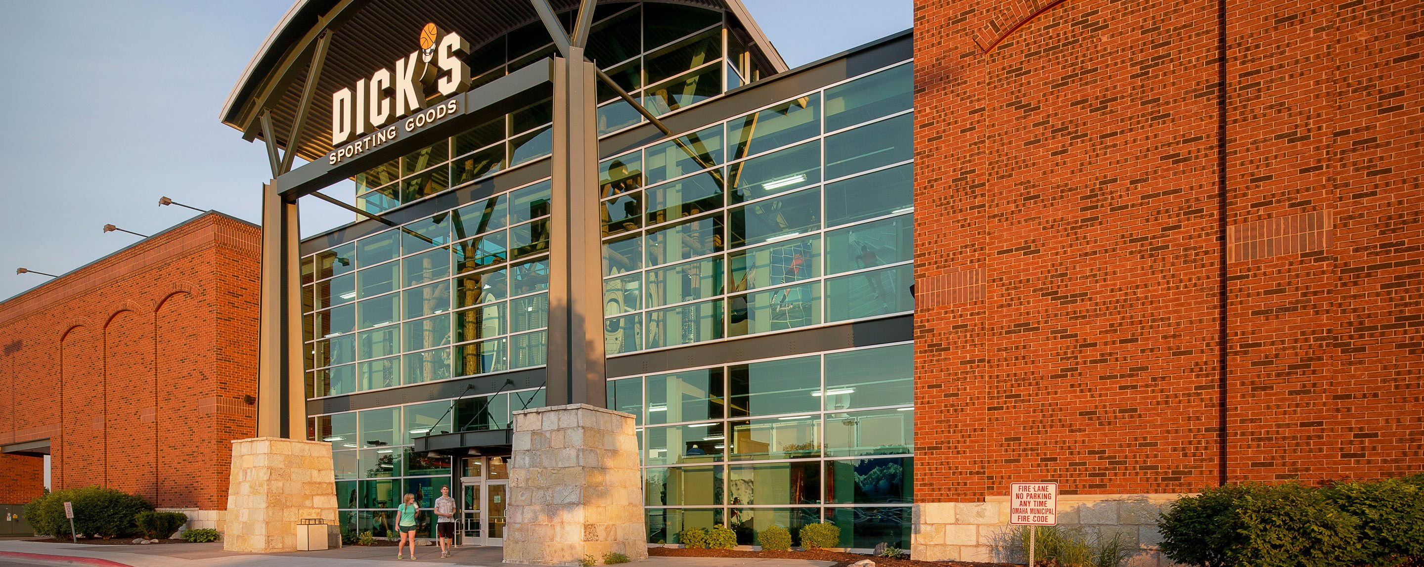 An exterior shot of a two story Dick's Sporting Goods. The storefront has large glass walls.