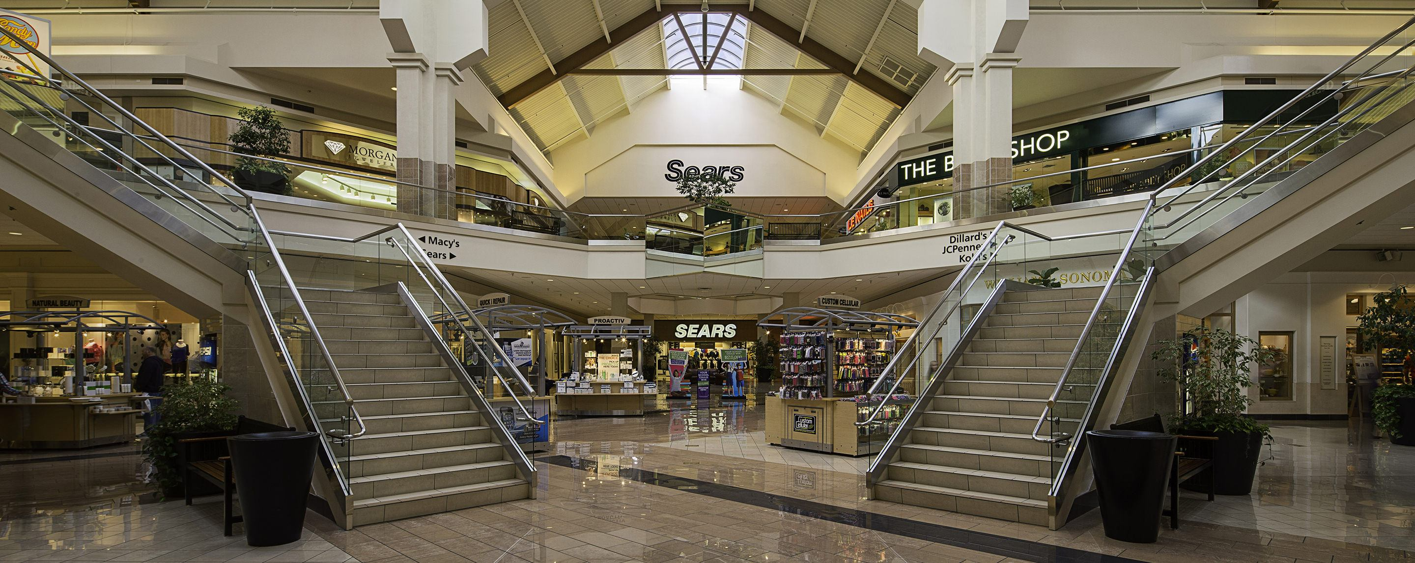 An indoor shopping mall with 2 staircases and a Sears visible.