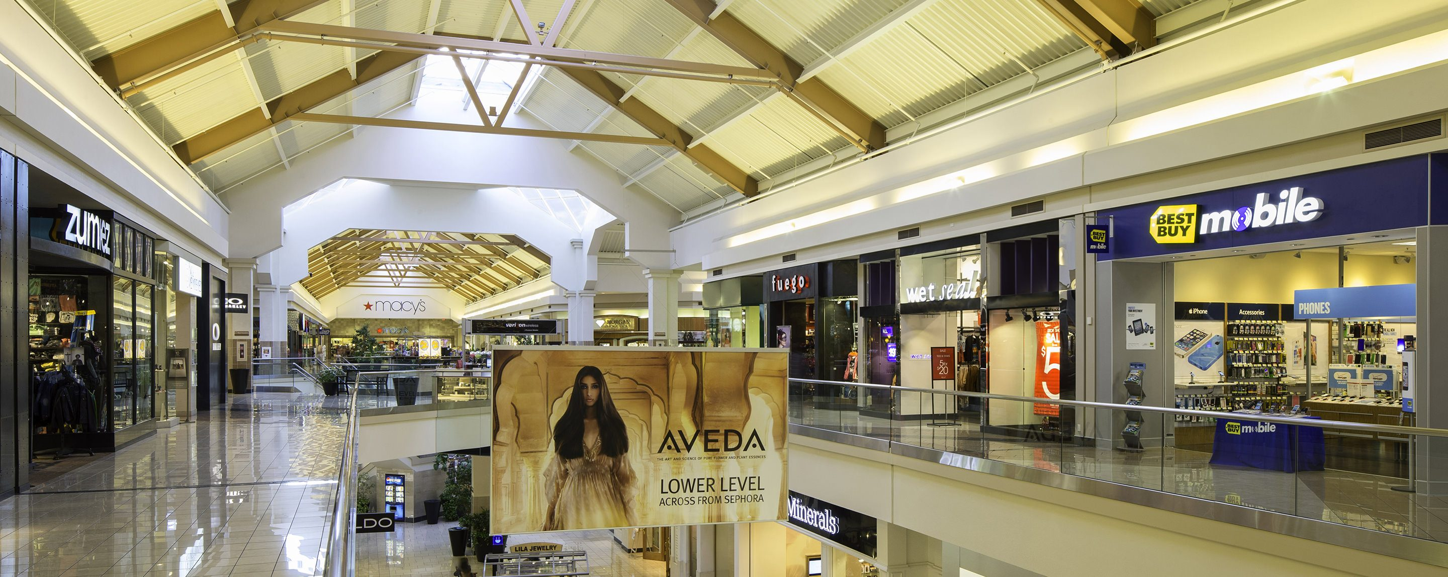 A variety of storefronts line the sides of a two story mall, including Aveda and Fuego.
