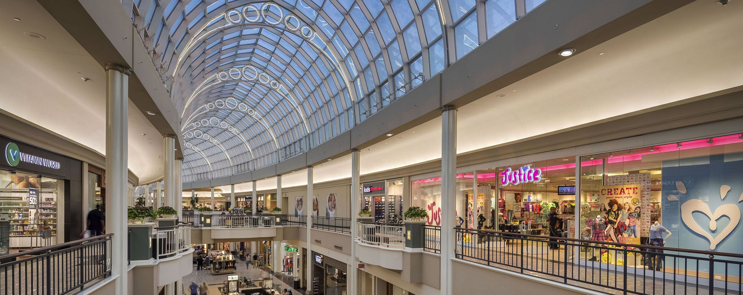 An interior shot of a mall with a curved glass ceiling. Several stores are on display, including Justice.