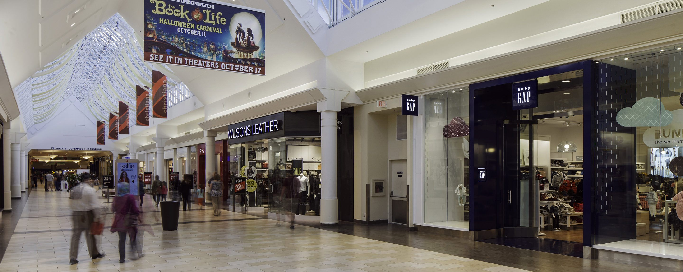 People walking by a GAP store inside of a mall.