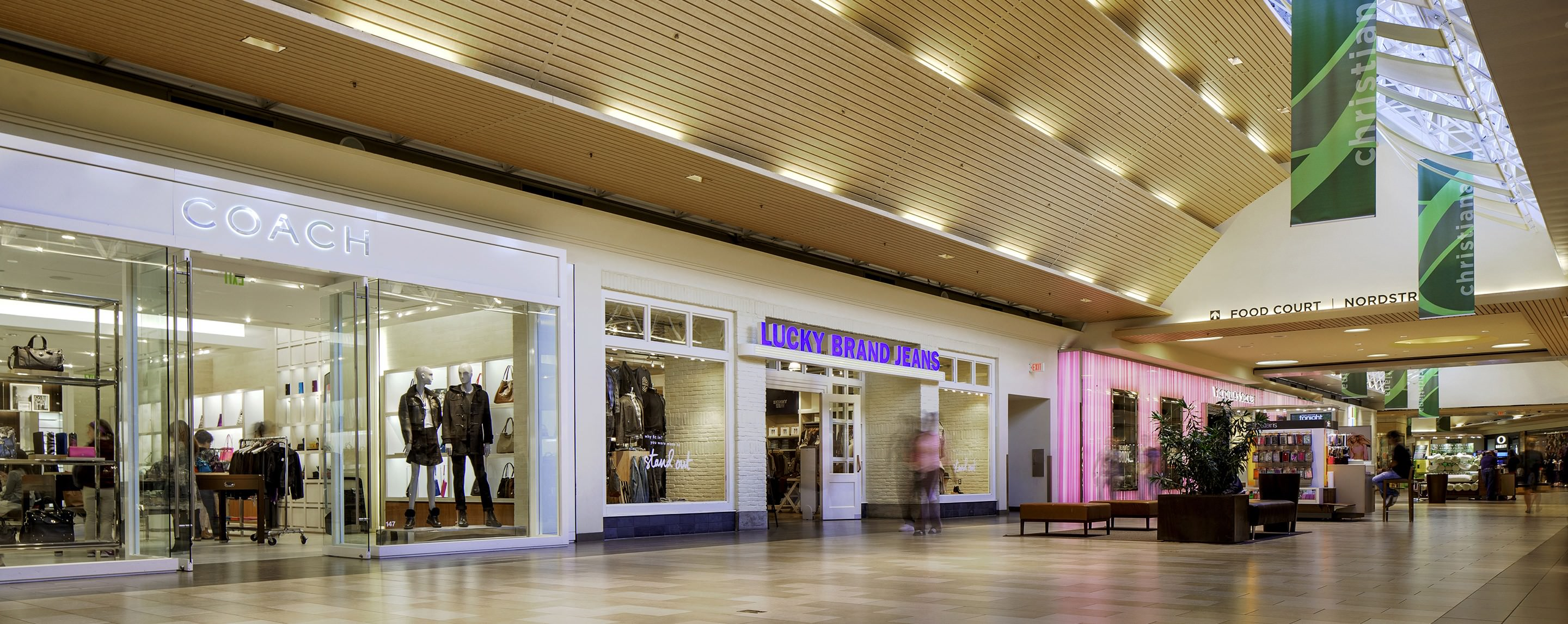 People walk past the Coach and Lucky Brand stores in the hall of an indoor mall.