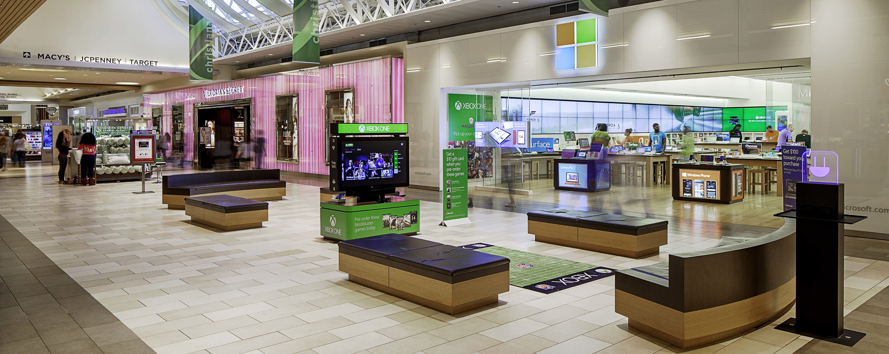 Sitting areas with televisions sit in the hallway of a shopping mall near a Victoria's Secret store.