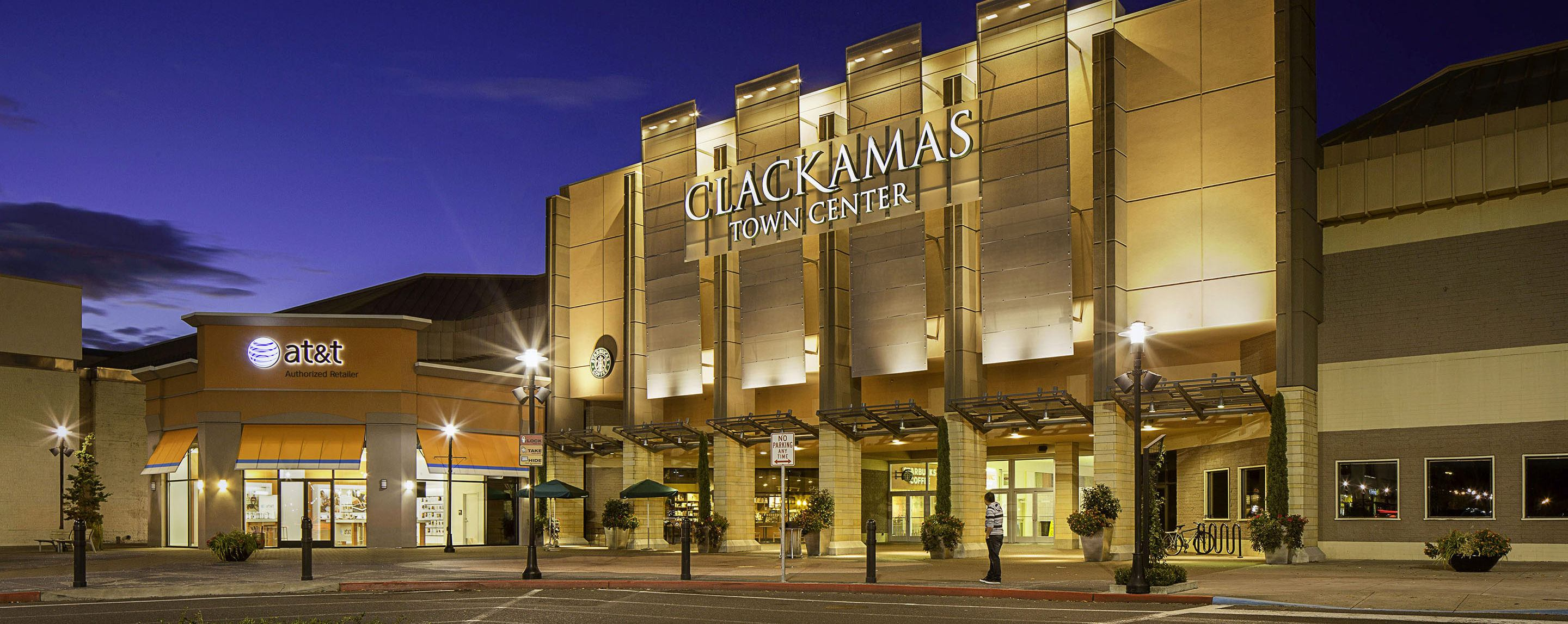 The building of the Clackamas Town Center is illuminated as it sits near an AT&T retail center at ni