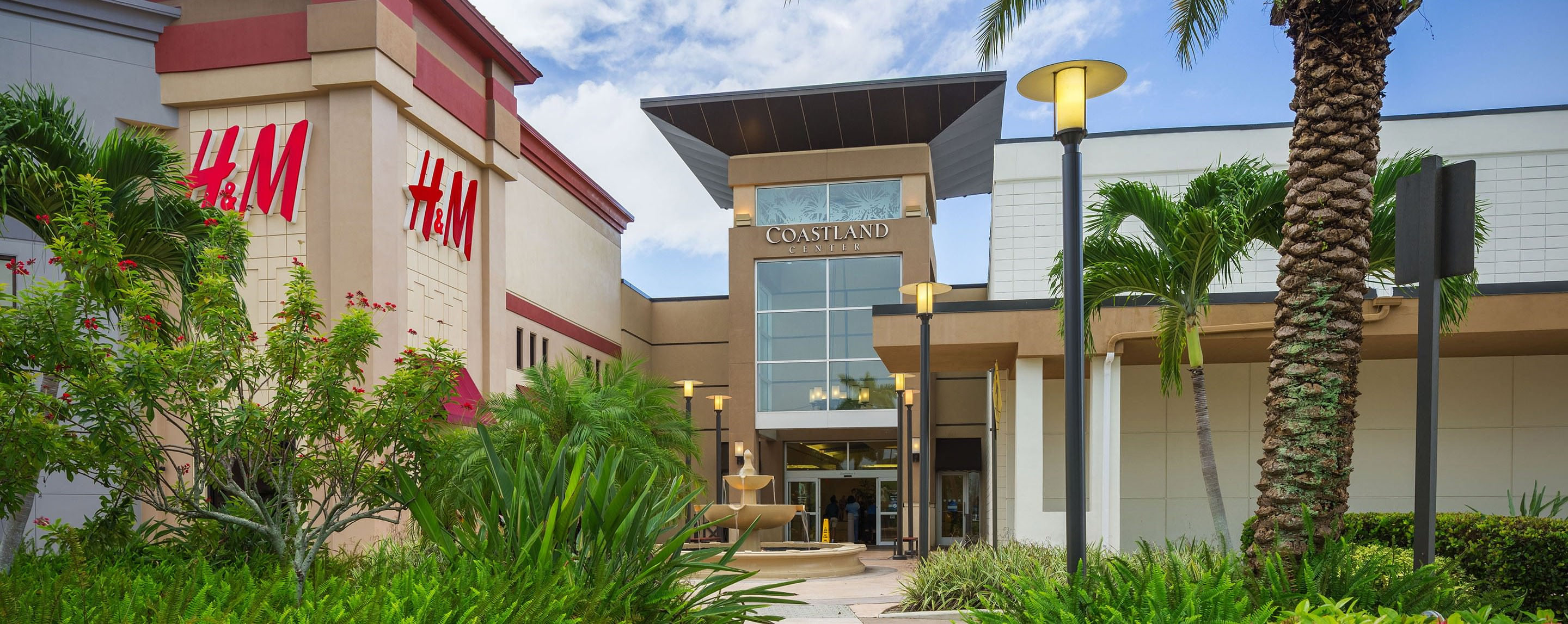 Entrance to Coastland Center. There's an H&M to the left and a fountain before the entryway.