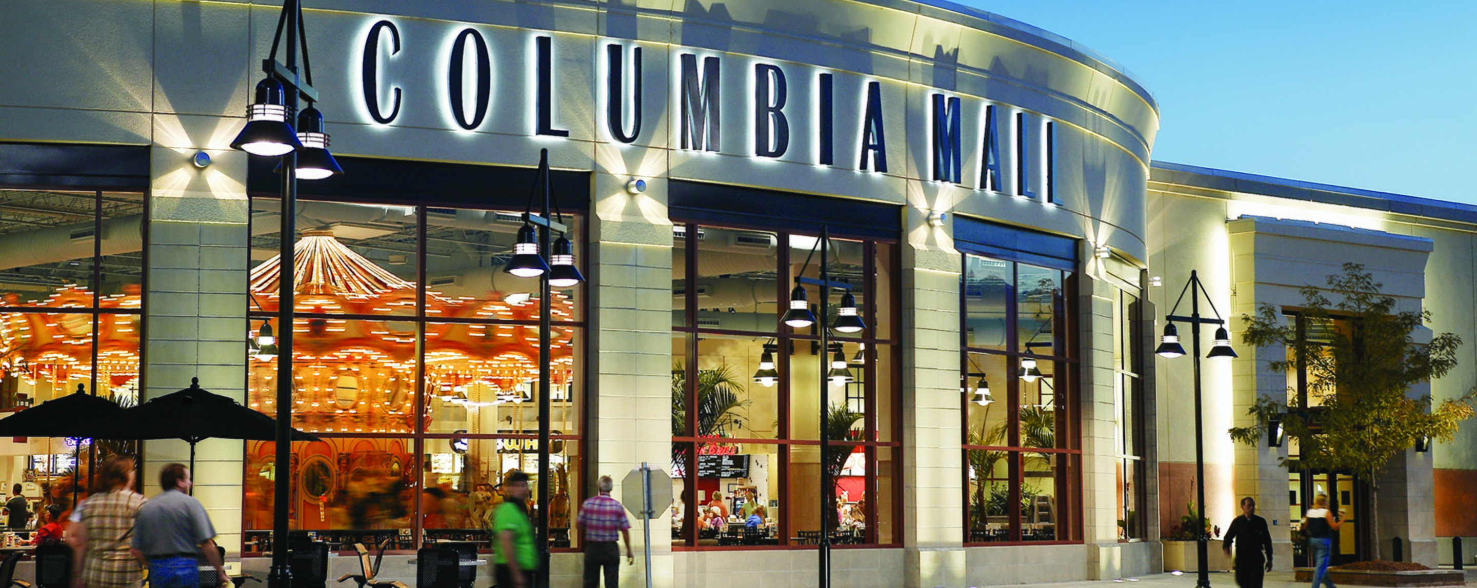 The exterior of the Columbia Mall. People walk by outside and sit at tables under umbrellas.