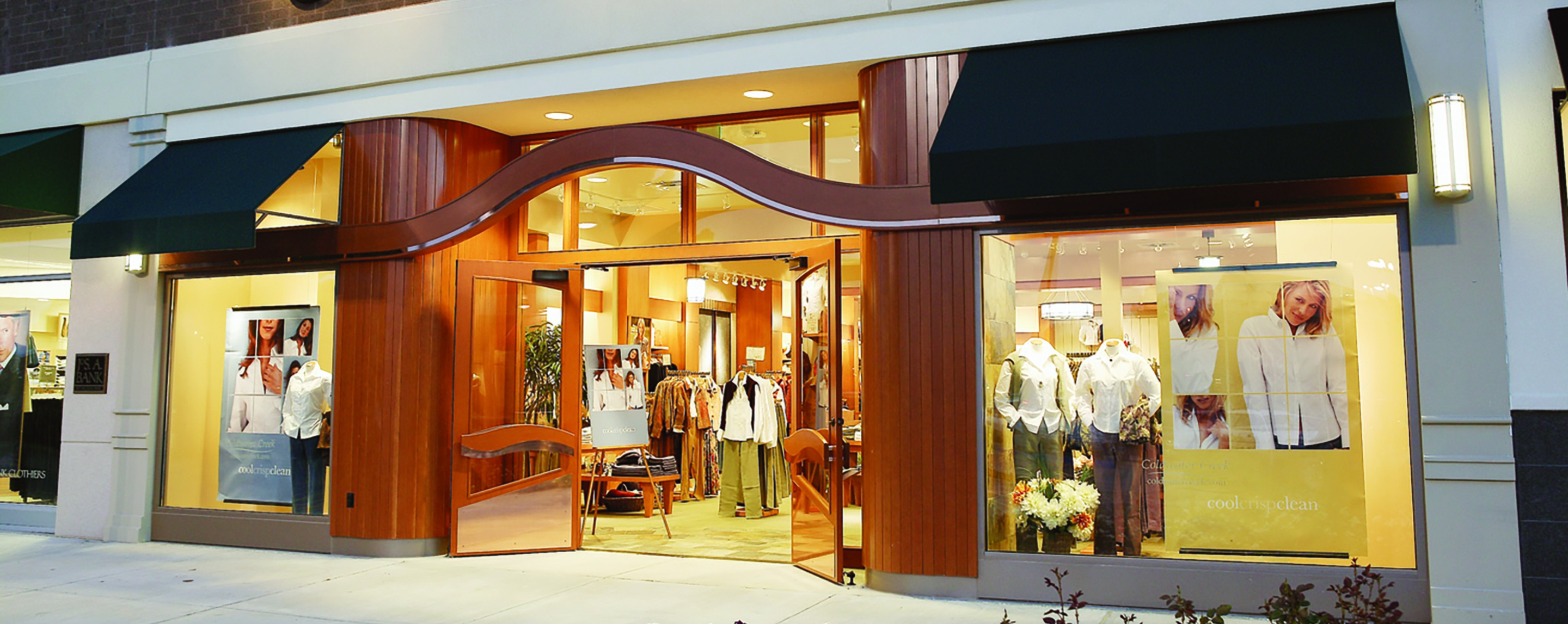 A well lit storefront features displays of women's clothing and large wooden columns.