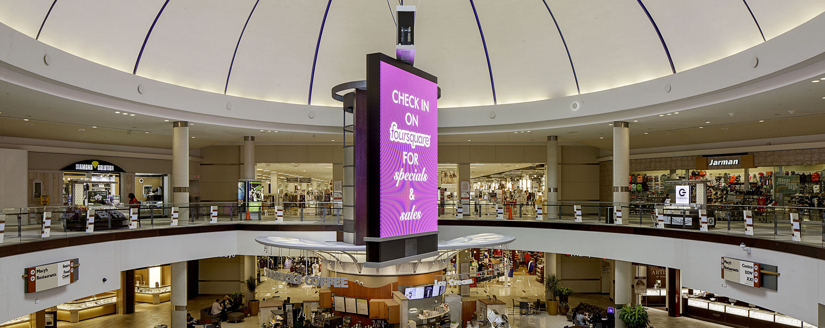 A purple banner hangs in the middle of a shopping center with stores such as Sears, Costco and Macy's.