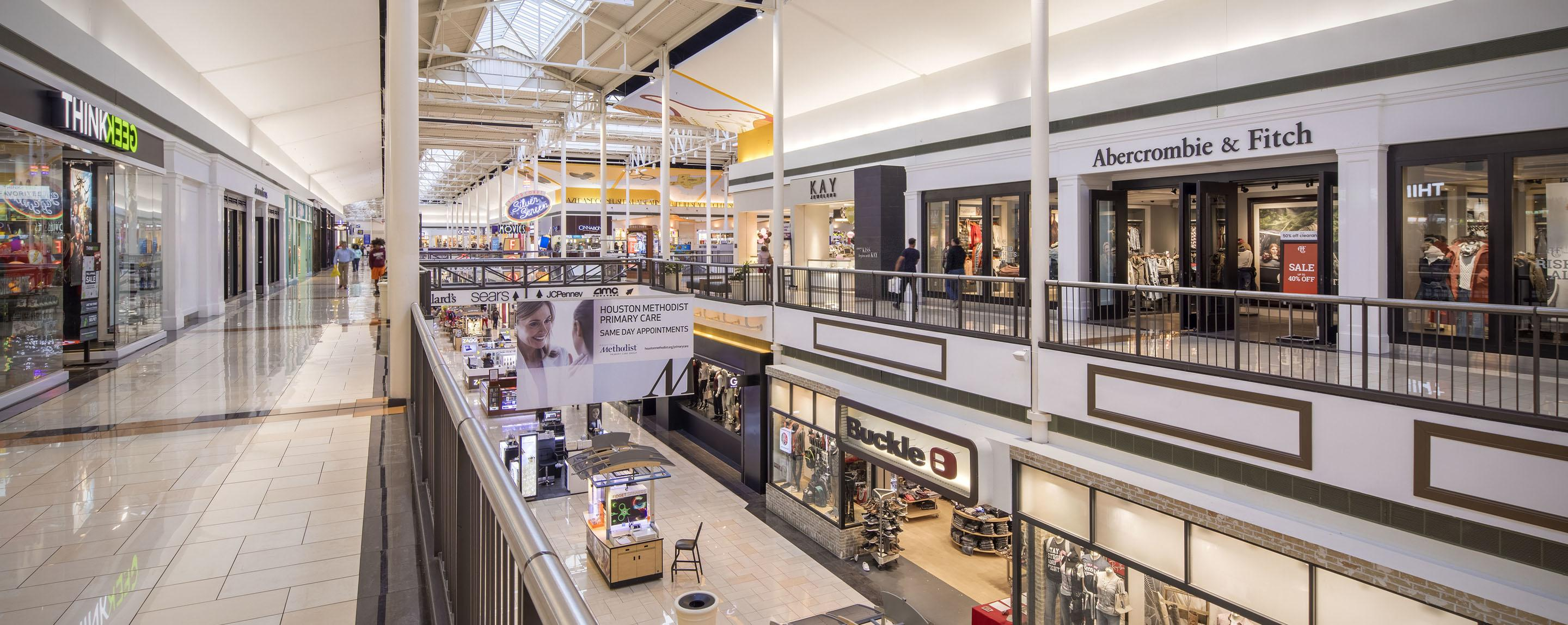 Abercrombie & Fitch, ThinkGeek, Buckly, and Kay Jewelers are retail stores in a two-story indoor mall with a skylight roof.
